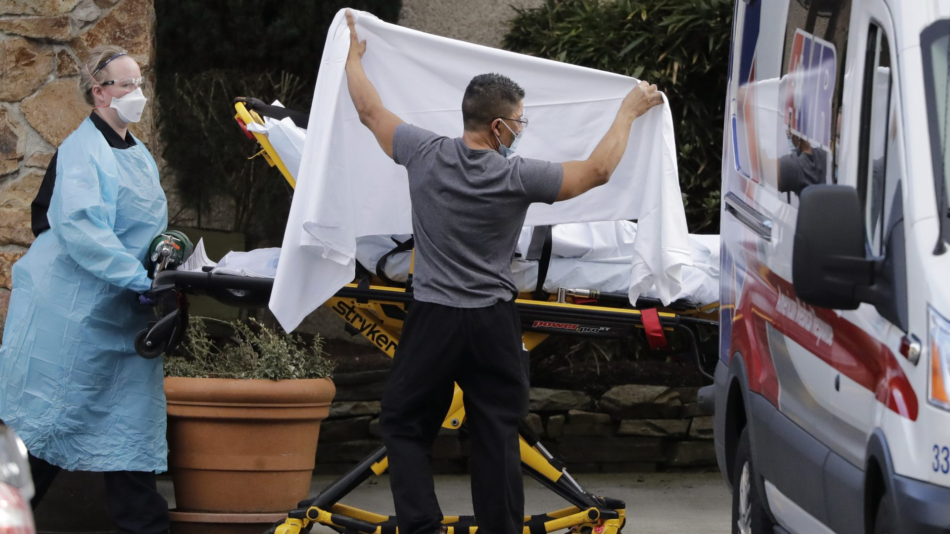A staff member holds a sheet as a privacy screen as a person on a stretcher is taken to an ambulance from Life Care, a nursing facility where dozens of people are being tested for the COVID-19 virus in Kirkland, Wash., northeast of Seattle.
