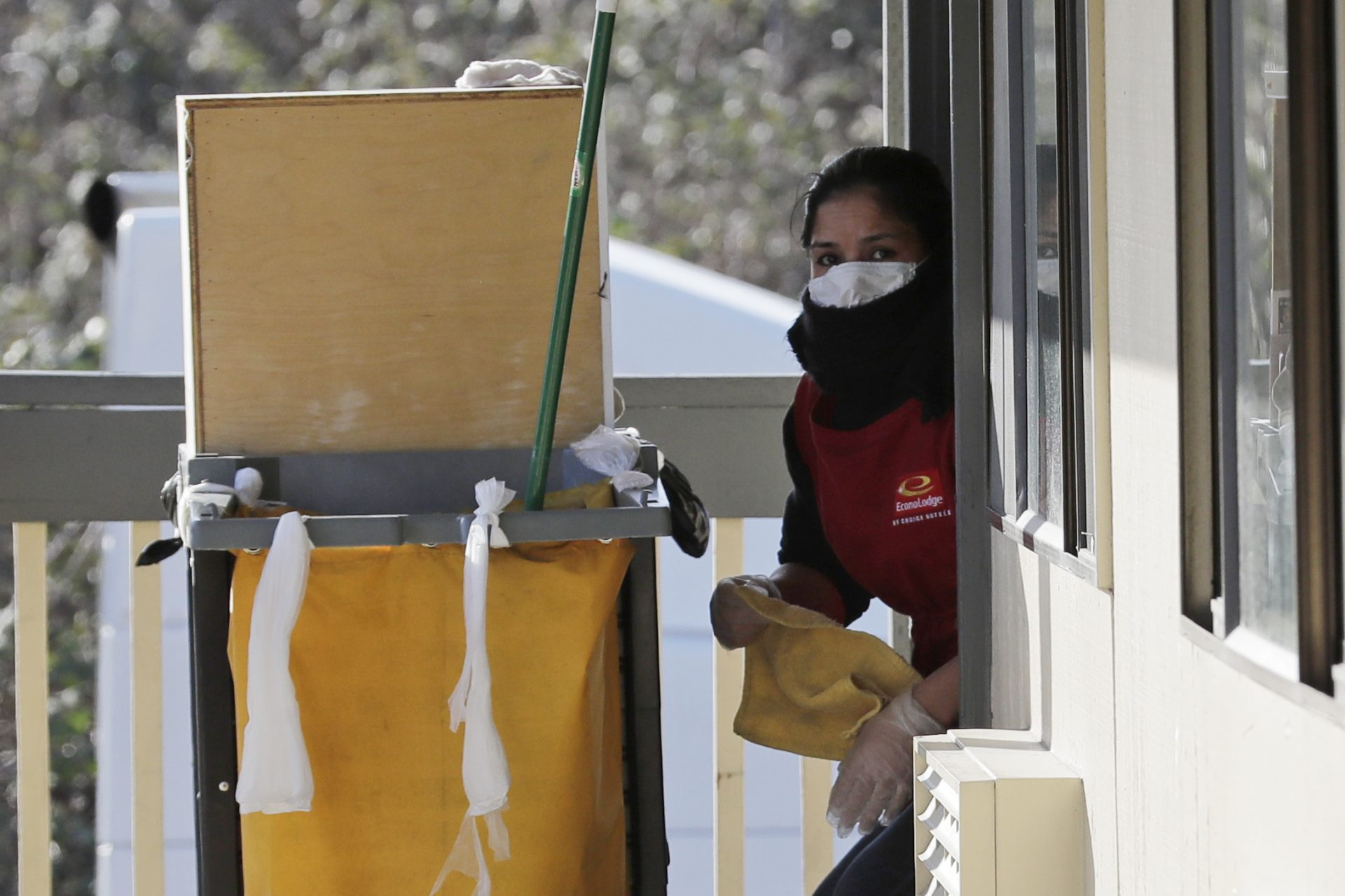 A housekeeping worker wears a mask as she cleans a room, Wednesday, March 4, 2020, at an Econo Lodge motel in Kent, Wash. King County Executive Dow Constantine said Wednesday that the county had purchased the 85-bed motel south of Seattle to house patients for recovery and isolation due to the COVID-19 coronavirus.