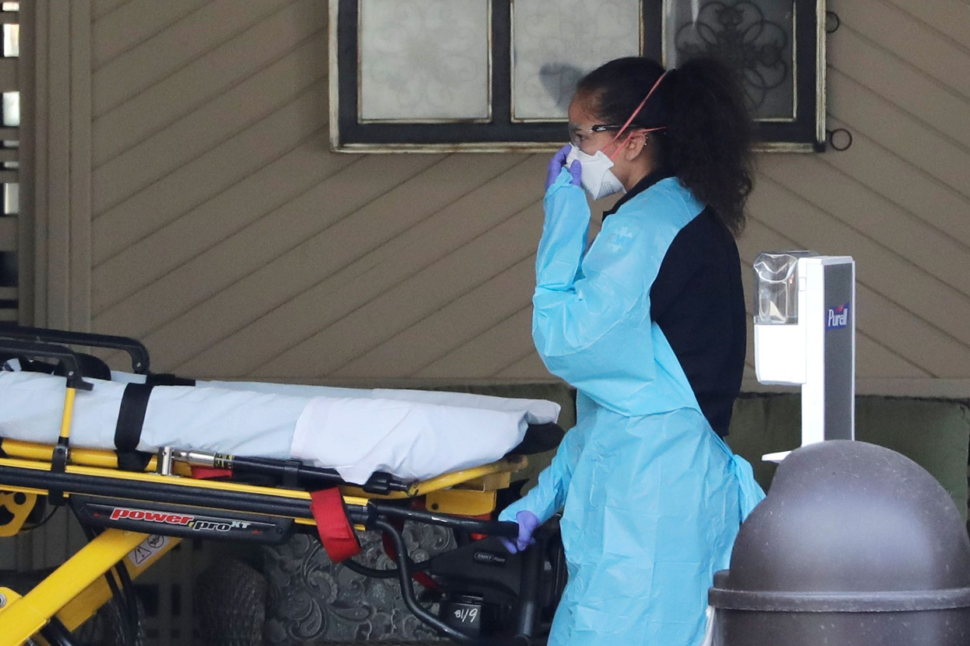 An ambulance worker adjusts her protective mask as she wheels a stretcher into a nursing facility where more than 50 people are sick and being tested for the COVID-19 virus, Saturday, Feb. 29, 2020, in Kirkland, Wash. Health officials reported two cases of COVID-19 virus connected to the Life Care Center of Kirkland. One is a Life Care worker, a woman in her 40s who is in satisfactory condition at a hospital, and the other is a woman in her 70s and a resident at Life Care who is hospitalized in serious condition. Neither have traveled out of the country.