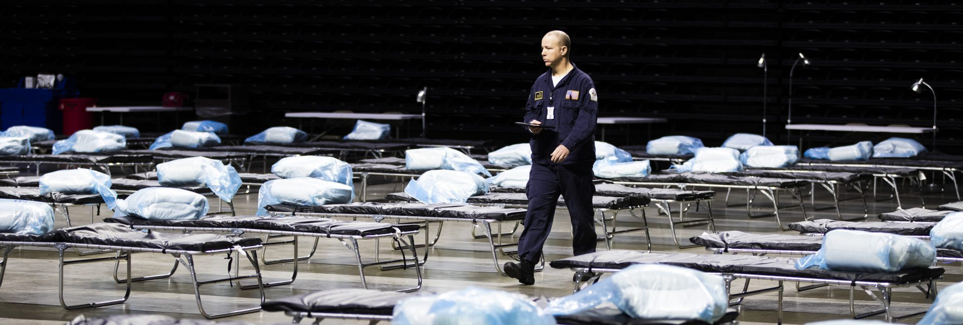 Pennsylvania Task Force 1 member Greg Rogalski walks amongst the beds of a Federal Medical Station for hospital surge capacity set up at Temple University's Liacouras Center in Philadelphia, Monday, March 30, 2020.