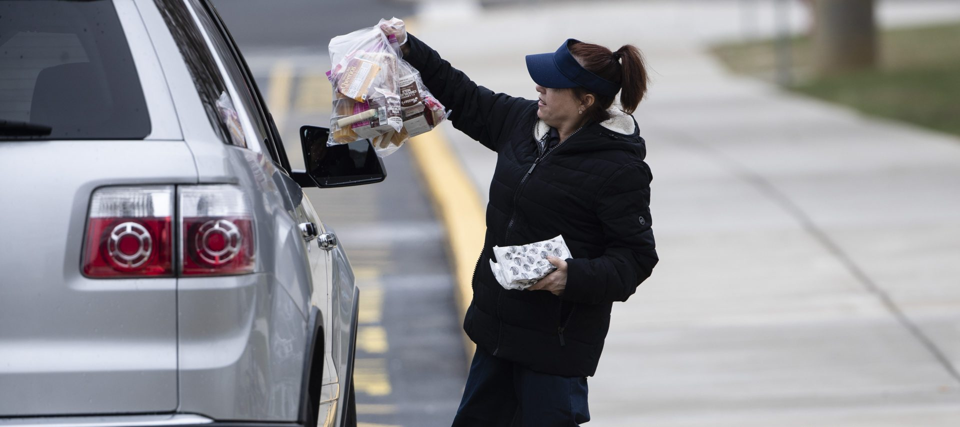Cafeteria worker Cathy Piluso hands out free meals at Bensalem High School in Bensalem, Pa., Thursday, March 19, 2020. Pennsylvania reported another big jump in confirmed coronavirus Thursday. The state Department of Health reported that cases topped 180, up 40%.