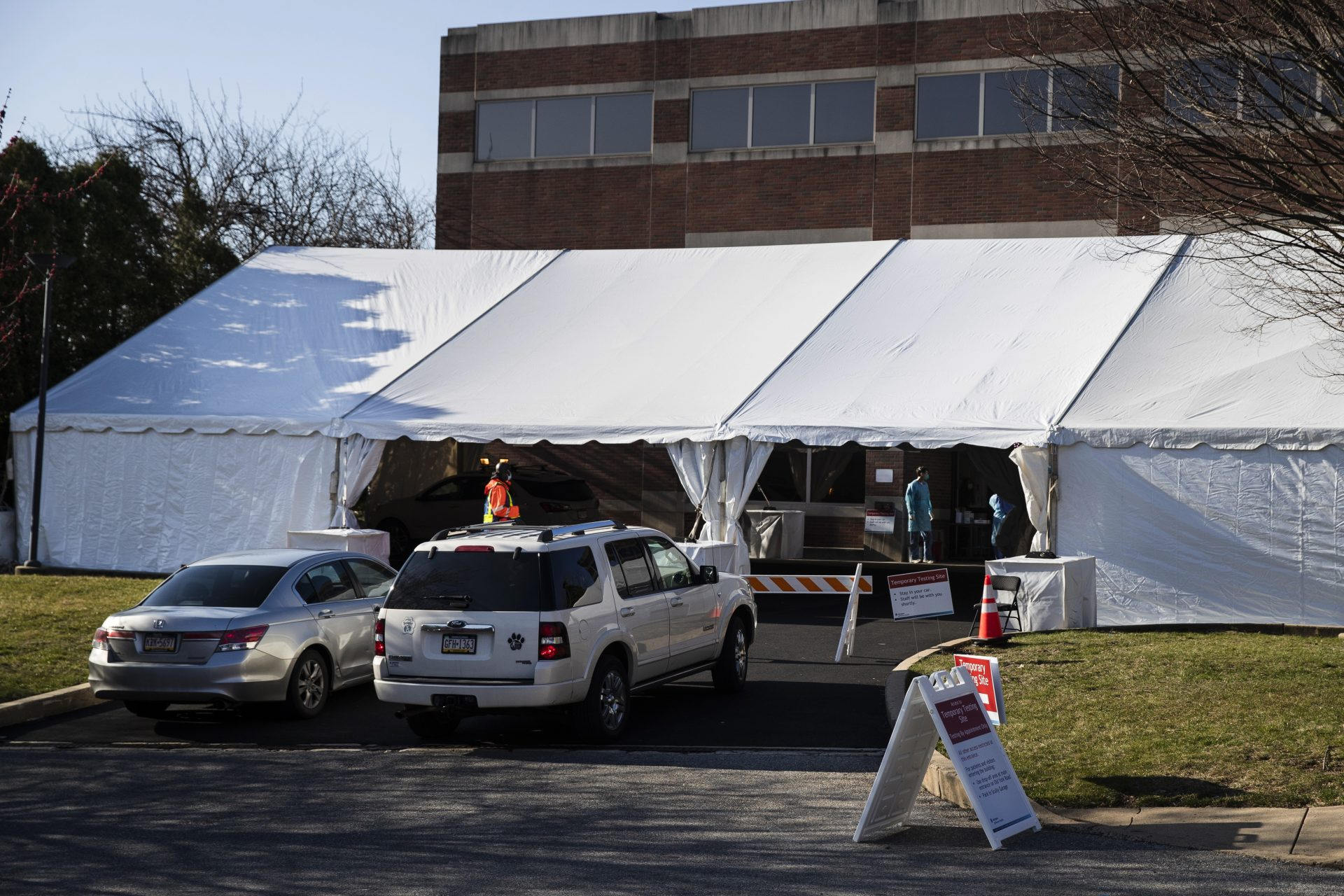 People in cars wait to enter a COVID-19 temporary testing site at Abington Hospital in Abington, Pa., Wednesday, March 18, 2020. For most people, the new coronavirus causes only mild or moderate symptoms. For some it can cause more severe illness.