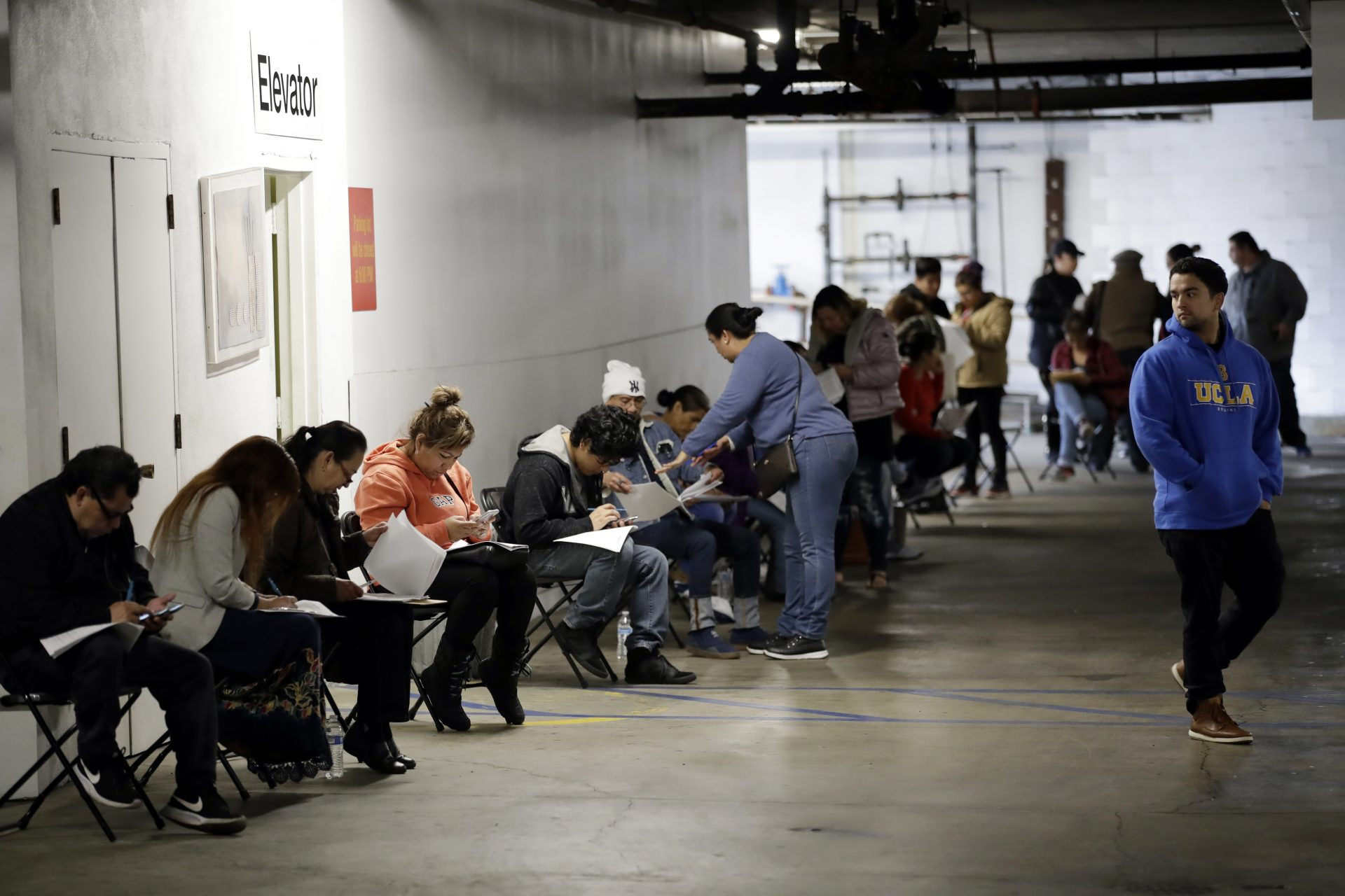 Unionized hospitality workers wait in line in a basement garage to apply for unemployment benefits at the Hospitality Training Academy Friday, March 13, 2020, in Los Angeles. Fearing a widespread health crisis, Californians moved broadly Friday to get in front of the spread of the coronavirus, shuttering schools that educate hundreds of thousands of students, urging the faithful to watch religious services online and postponing or scratching just about any event that could attract a big crowd.