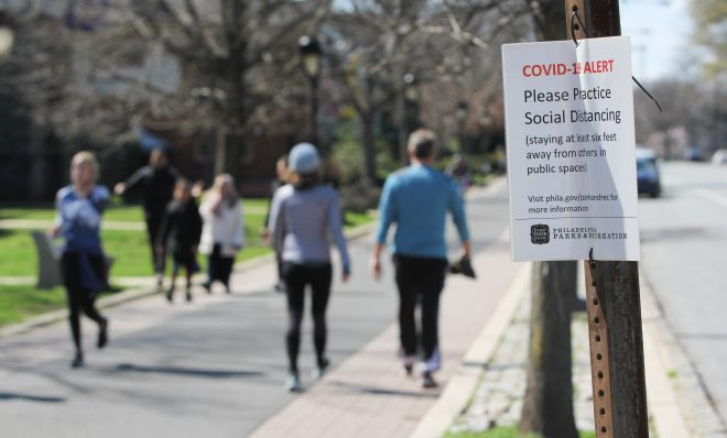 Signs posted along Philadelphia's Schuylkill River Trail caution users to keep six feet away from others to prevent the spread of COVID-19.