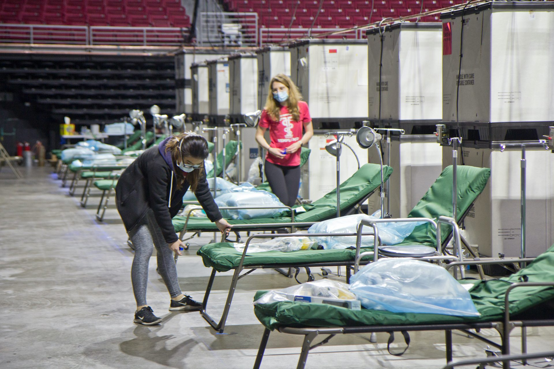 Temple University medical students work to prepare 180 beds at the Liacouras Center, which is set to open April 16 to accommodate an overflow of COVID-19 patients in Philadelphia.