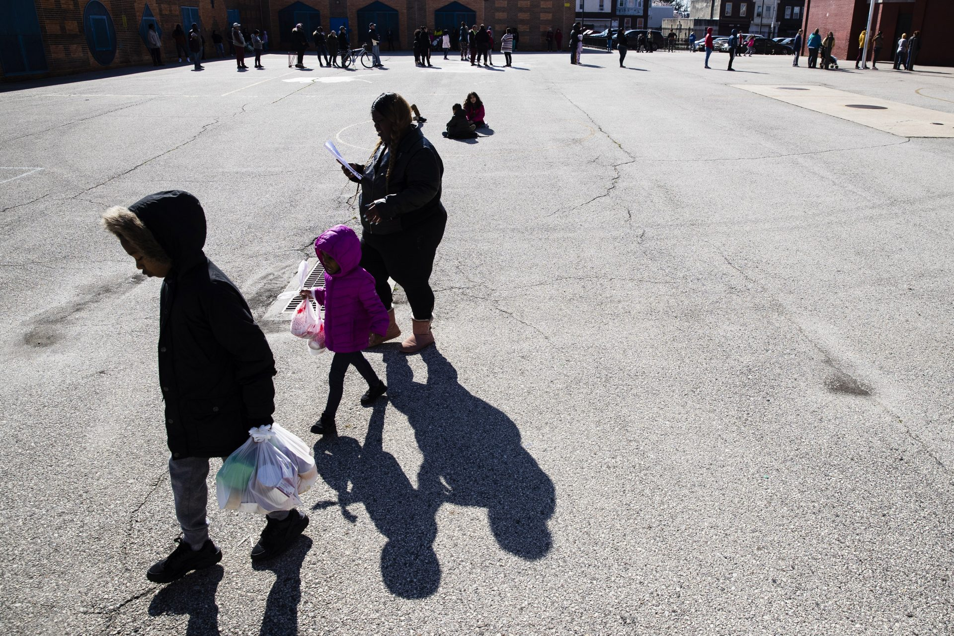 A woman and children walk away from the John H. Webster Elementary School carrying donated food and educational materials, in Philadelphia, Thursday, March 26, 2020.