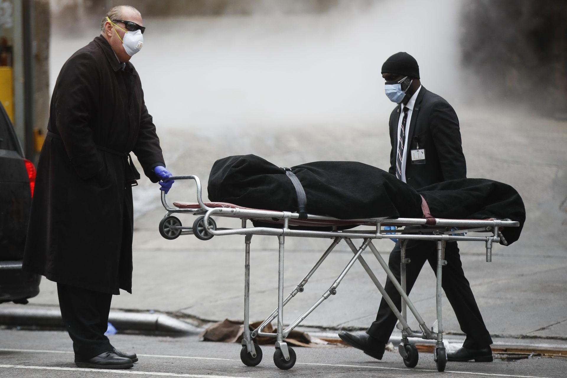 A funeral director wears personal protective equipment due to COVID-19 concerns while collecting a body at The Brooklyn Hospital Center, Thursday, April 9, 2020, in the Brooklyn borough of New York.