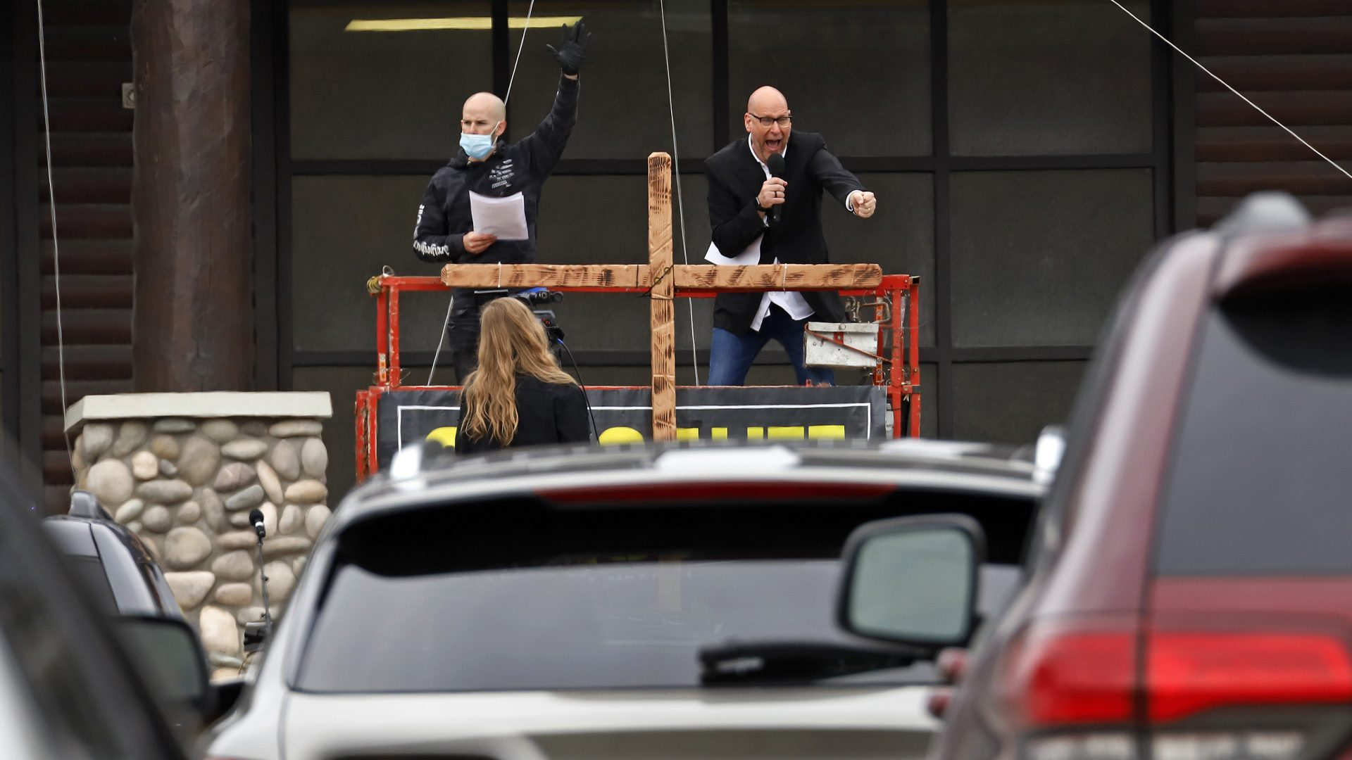 Pastor Bruce Schafer, top right, preaches from a scissor lift during the first of two drive-in Easter services held by Grace Life Church in a parking lot in Monroeville, Pa., Sunday, April 12, 2020.