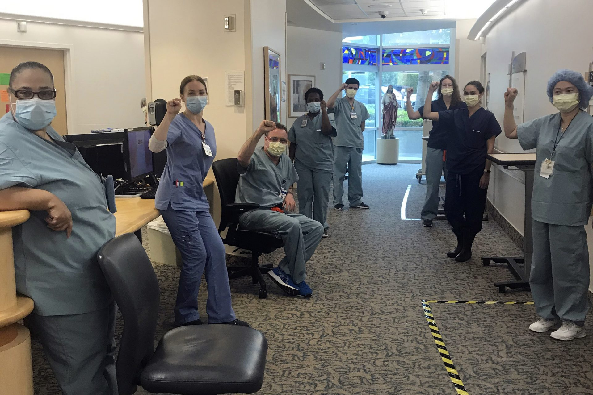 In this image provided by Lizabeth Baker Wade, nurses at Providence Saint John's Health Center in Santa Monica, Calif., on April 10, 2020, raise their fists in solidarity after telling managers they can't care for COVID-19 patients without N95 respirator masks to protect themselves. The hospital has suspended ten nurses from the ward, but has started providing nurses caring for COVID-19 patients with N95 masks