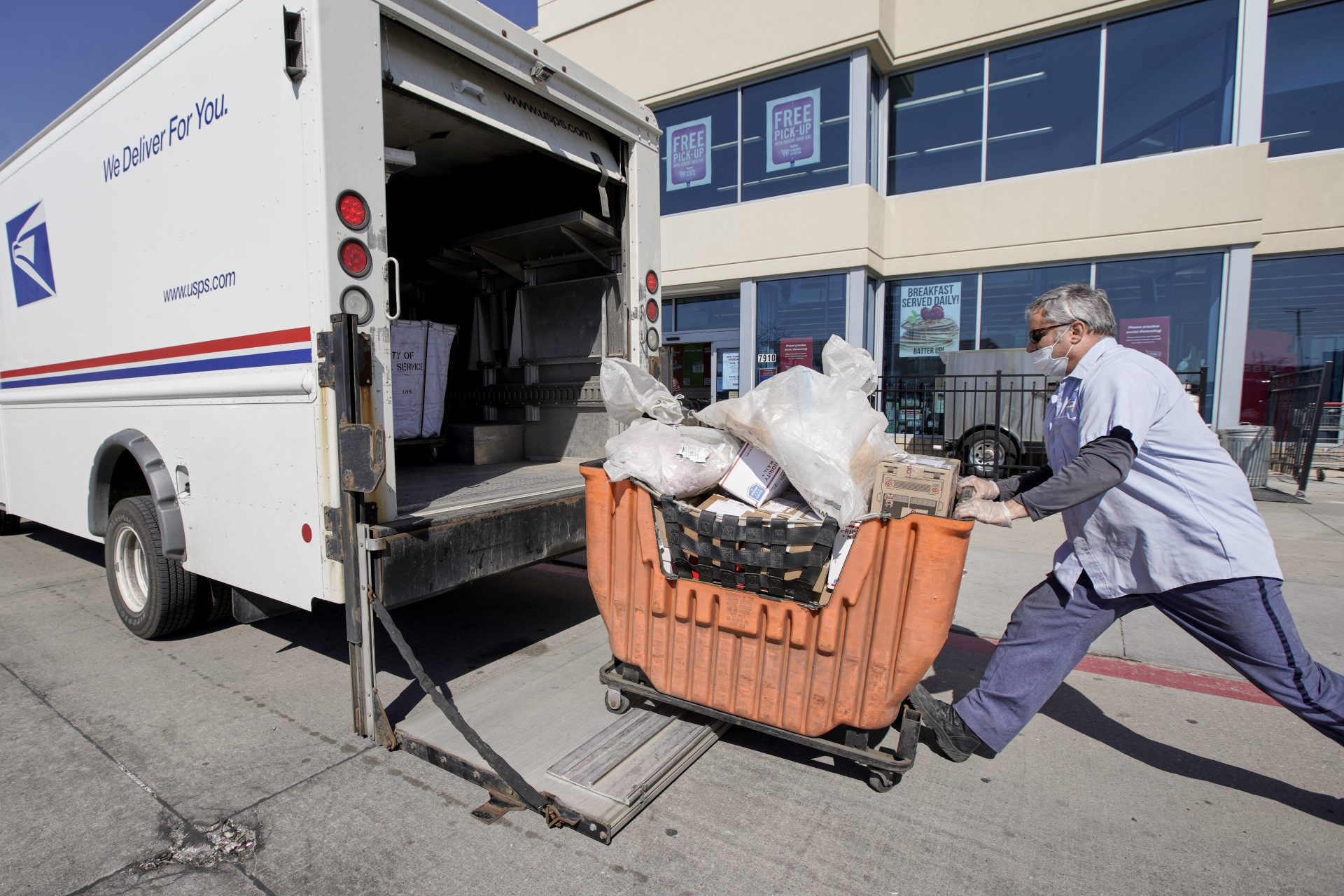 A postal worker wears protective gear against the coronavirus as he collects articles of mail outside a supermarket in Omaha, Neb., Friday, April 10, 2020.