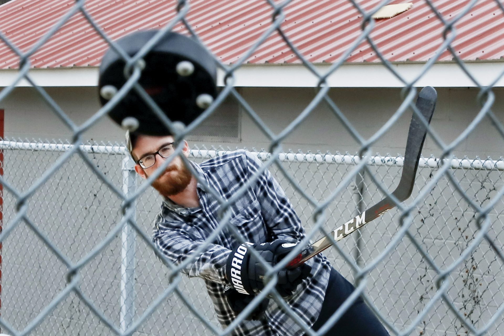 Jason Dapper, shoots a street hockey puck at the fence in one of the tennis courts at the local park as he practices his hockey skills with his wife, Friday, March 27, 2020, in Zelienople, Pa. The couple said they have taken to the park since the local rinks have closed with the outbreak of COVID-19.