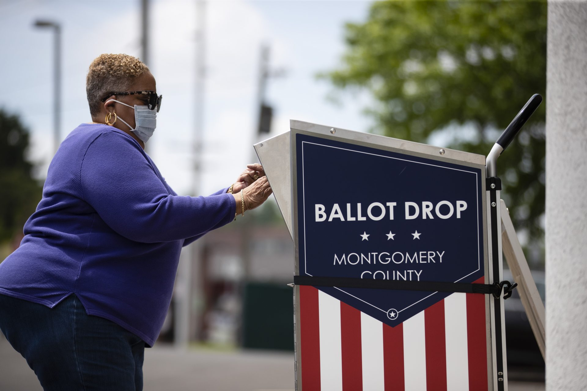 A voter drops off their mail-in ballot prior to the primary election, in Willow Grove, Pa., Wednesday, May 27, 2020.