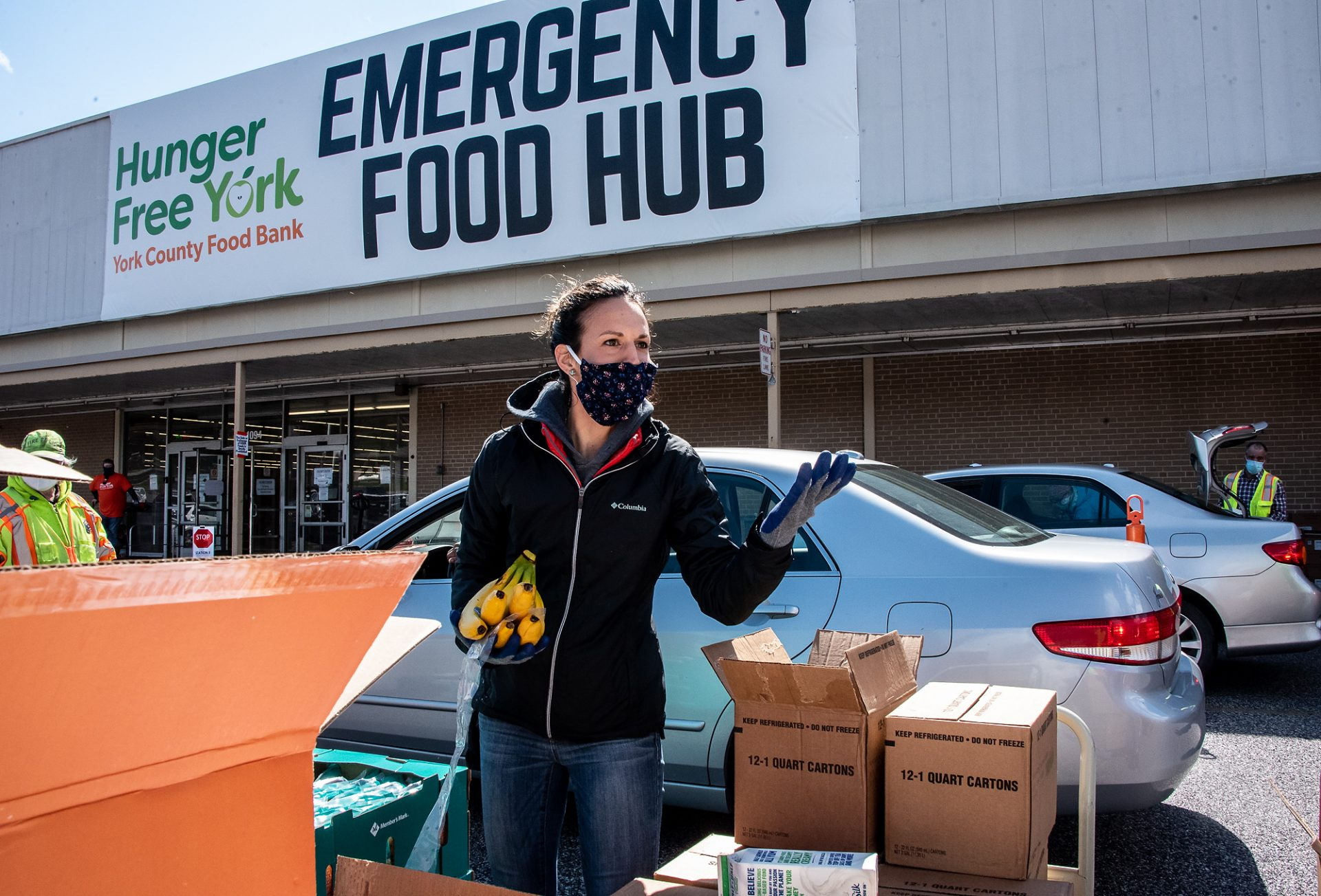 A volunteer helps prepare food boxes at a distribution event in York County.