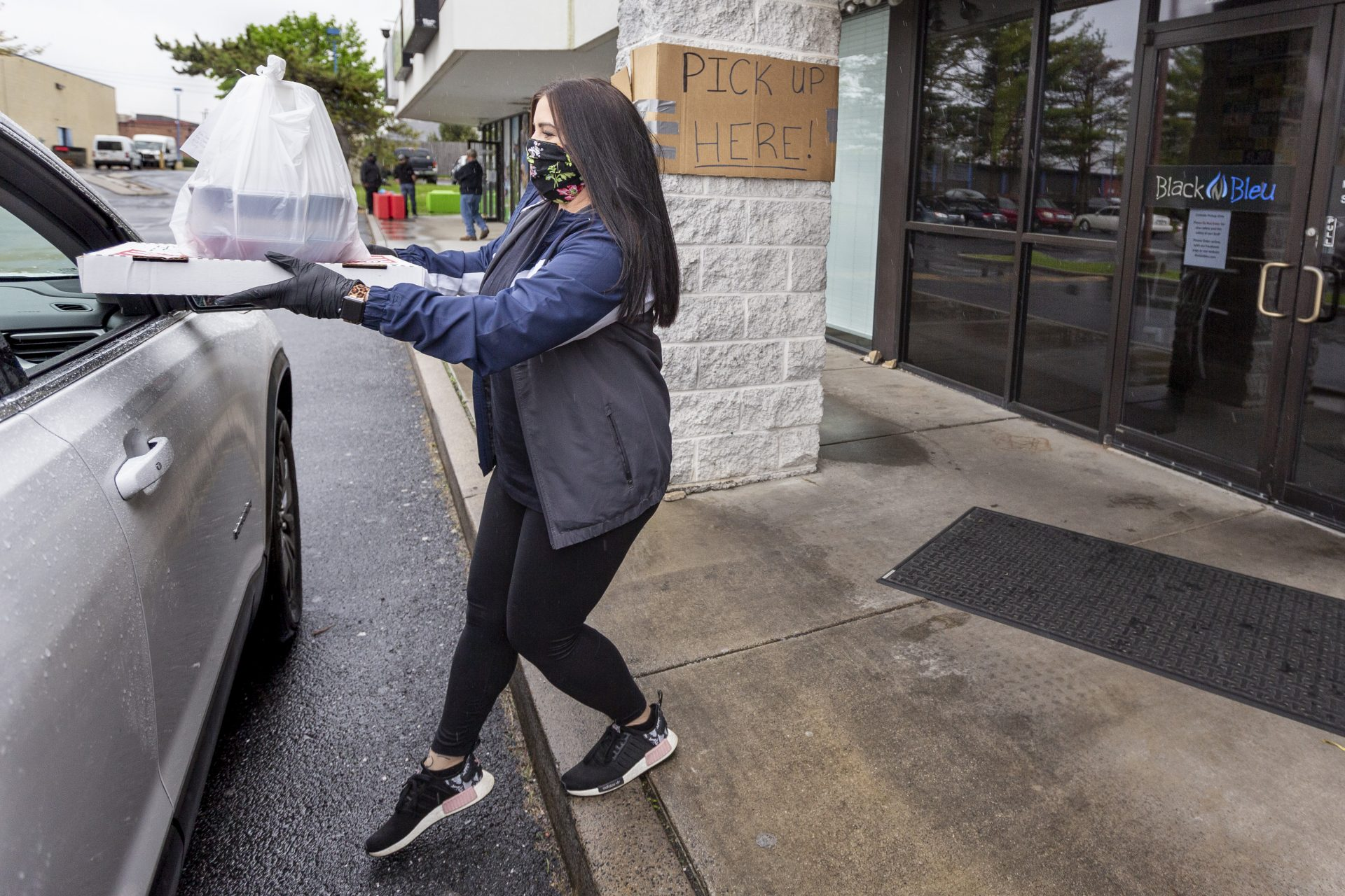 Jordan Copenhaver delivers take out to a car outside of Black 'n Bleu in Mechanicsburg on May 6, 2020. The restaurant has adapted to serving take out only during the COVID-19 pandemic.
