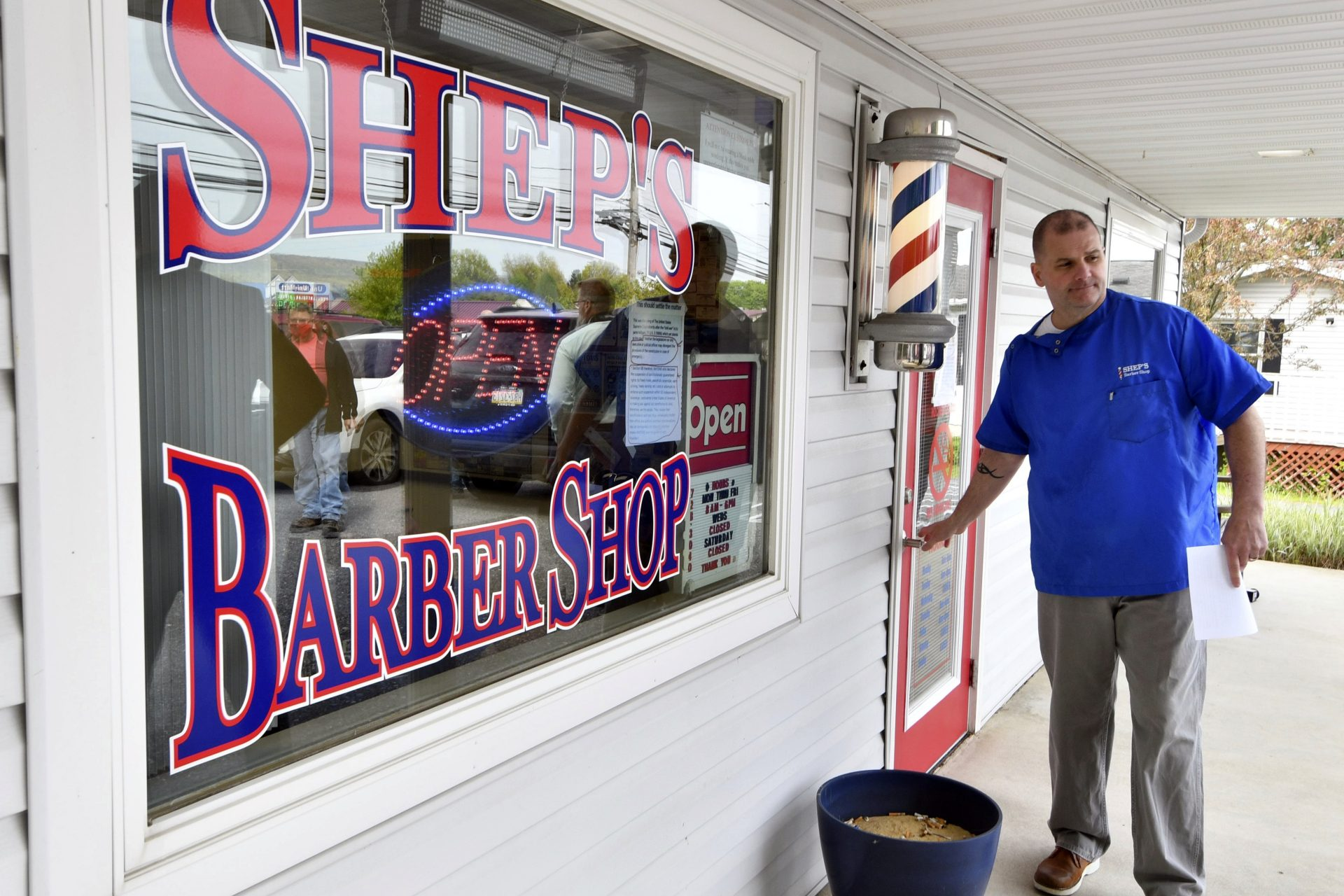 Brad Shepler, a barber who resumed cutting hair despite it being prohibited under Pennsylvania Gov. Tom Wolf's coronavirus shutdown orders, walks out of his barber shop to hold a new conference with local state lawmakers, Thursday, May 14, 2020 in Enola, Pa. Shepler also received a warning letter from the state's licensing agency.