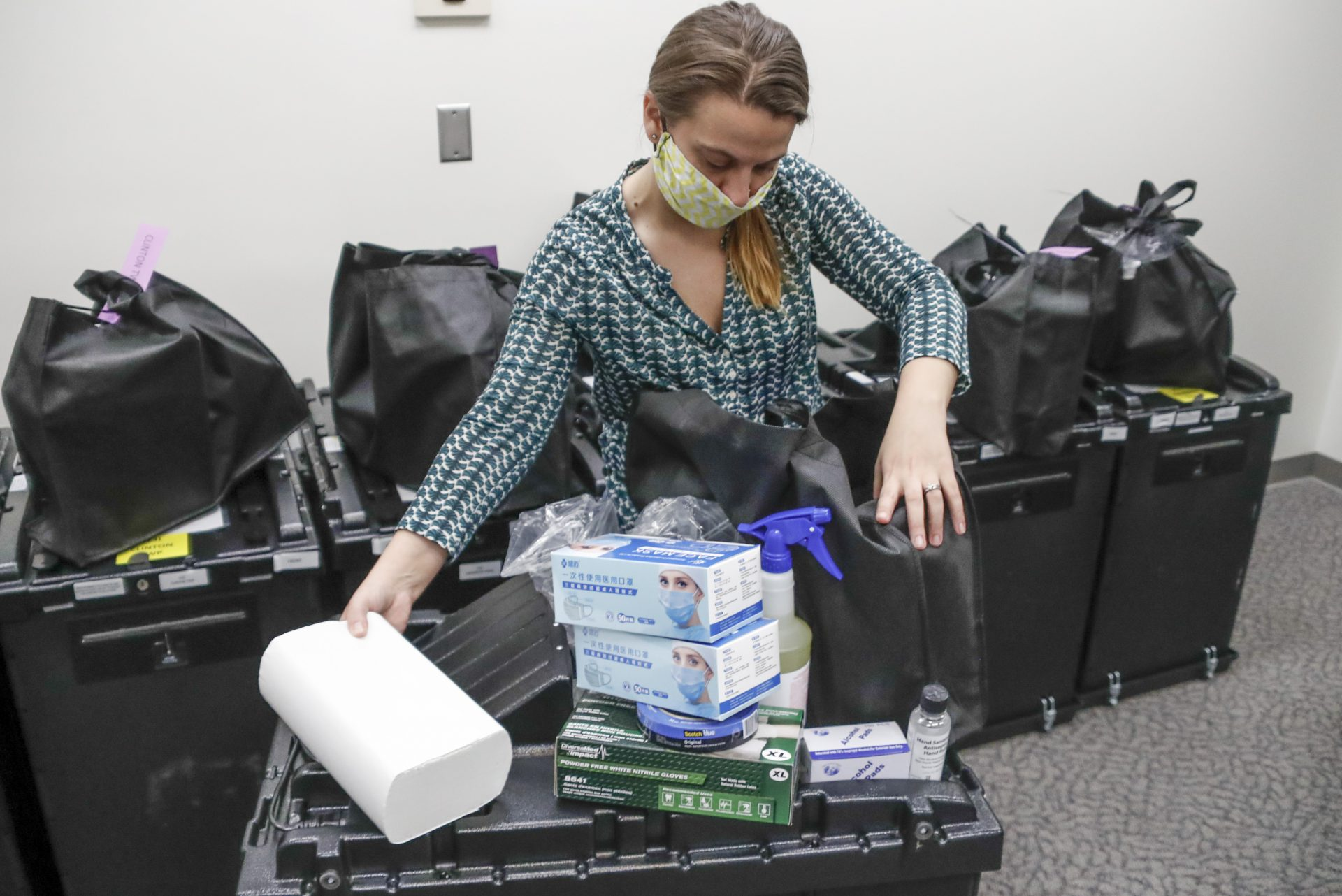 Butler County Bureau of Elections Registrar, Chantell McCurdy packs one of the COVID-19 cleaning and preparedness precinct kits with equipment as protective masks, gloves, hand sanitizers, wipes and sprays for sanitizing, for poll workers for Pennsylvania's June 2nd Primary election before they are sent out from the offices Thursday, May 28, 2020, in Butler, Pa.