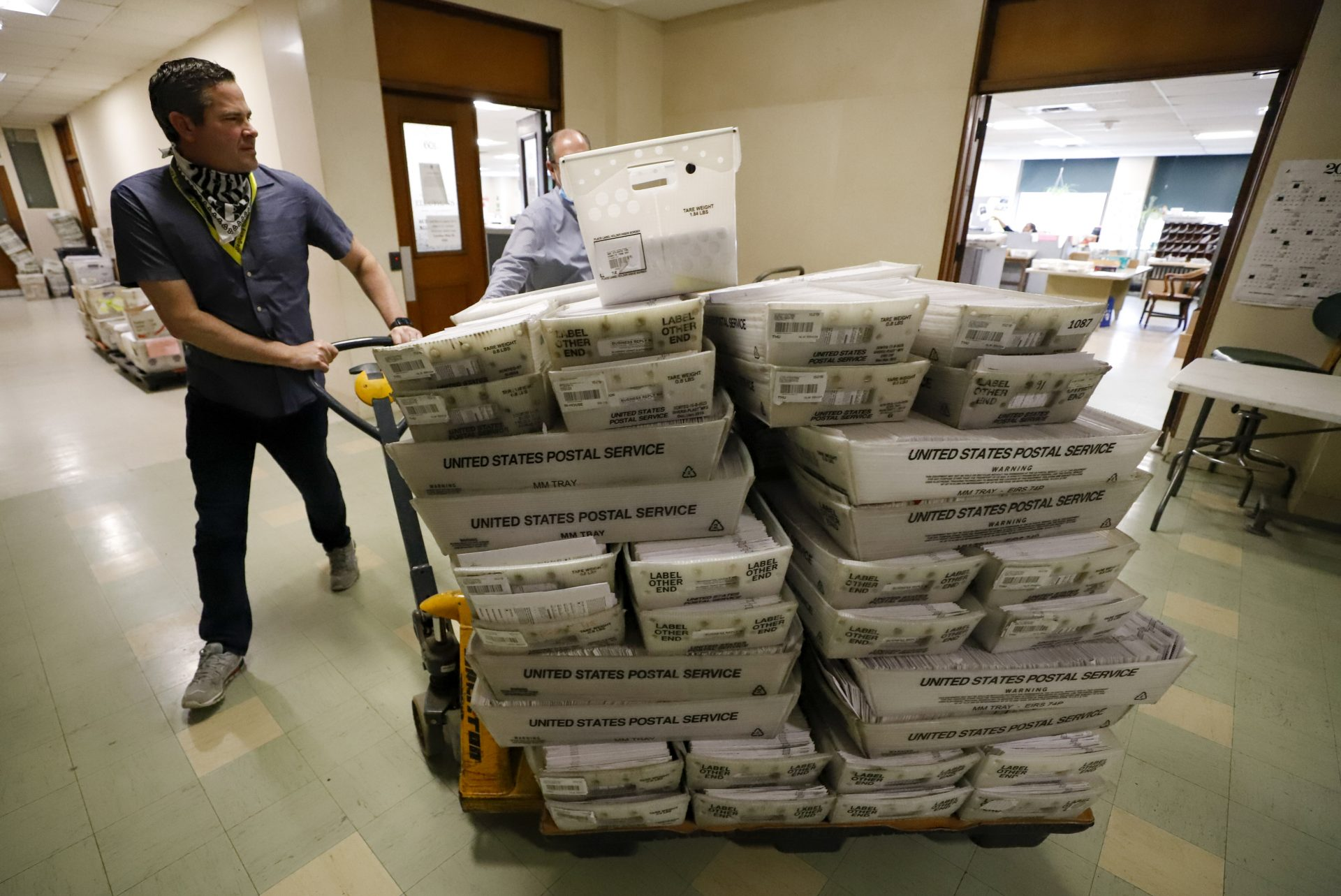 Chet Harhut, deputy manager, of the Allegheny County Division of Elections, wheels a dolly loaded with mail-in ballots, at the division of elections offices in downtown Pittsburgh Wednesday, May 27, 2020. The once-delayed June 2, Pennsylvania primary will feature legislative and congressional races, a first run for some new paper-record voting systems and the inaugural use of newly legalized mail-in ballots.