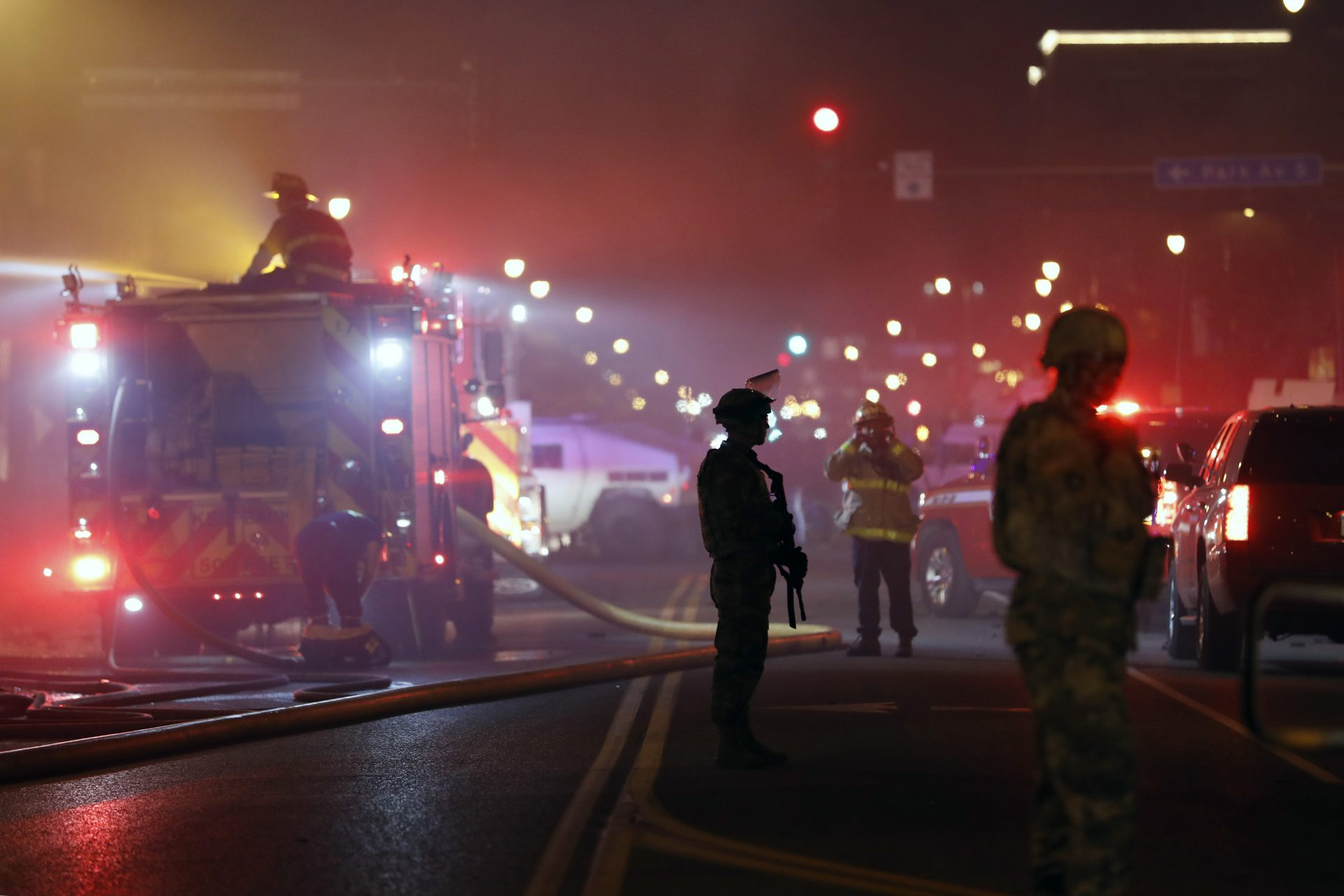 The National Guard standby as firefighters extinguish a blaze at a gas station Friday, May 29, 2020, in Minneapolis. Protests continued following the death of George Floyd, who died after being restrained by Minneapolis police officers on Memorial Day.