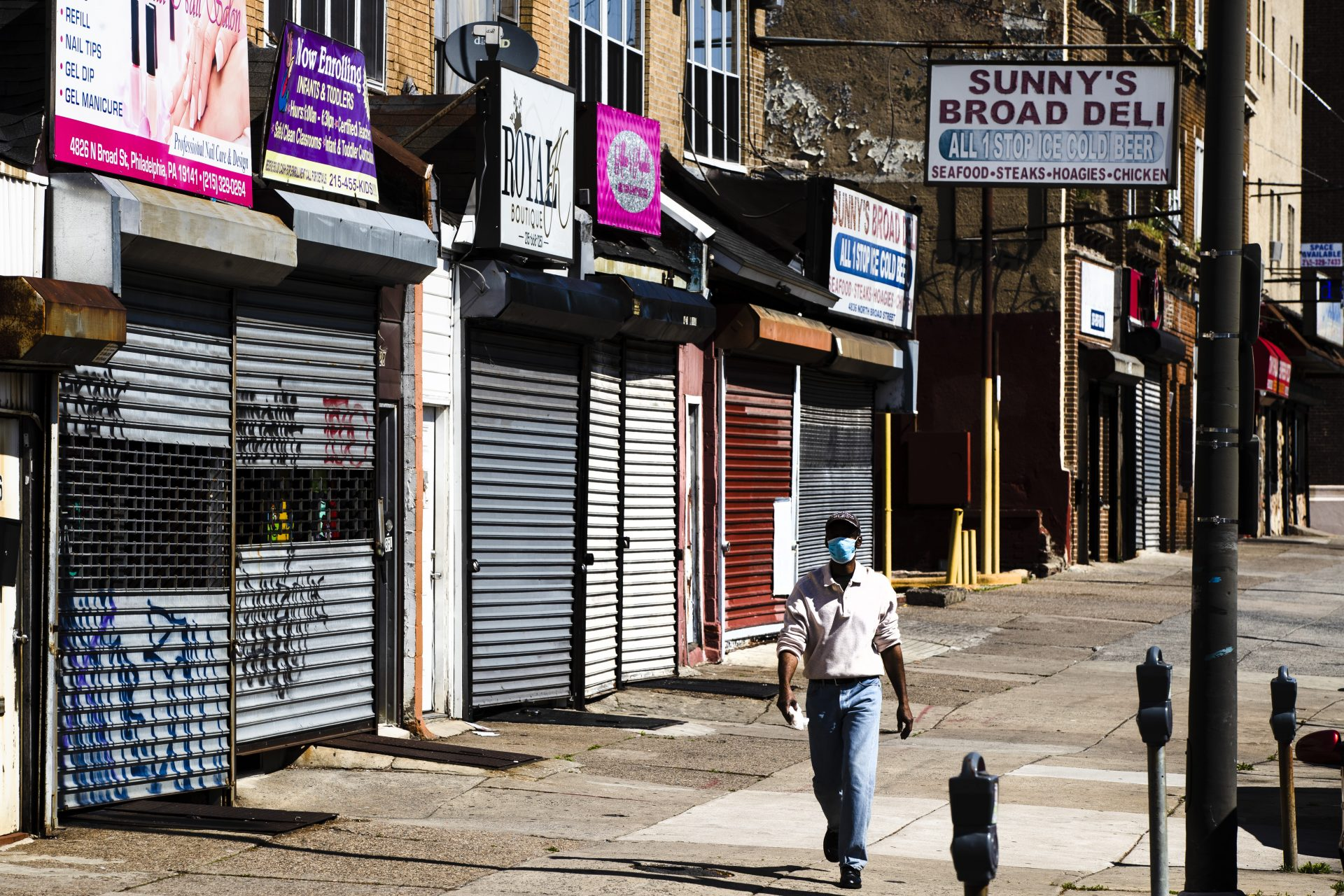A person wearing a protective face mask as a precaution against the coronavirus walks past stuttered businesses in Philadelphia, Thursday, May 7, 2020. Nearly 3.2 million laid-off workers applied for unemployment benefits last week as the business shutdowns caused by the viral outbreak deepened the worst U.S. economic catastrophe in decades.