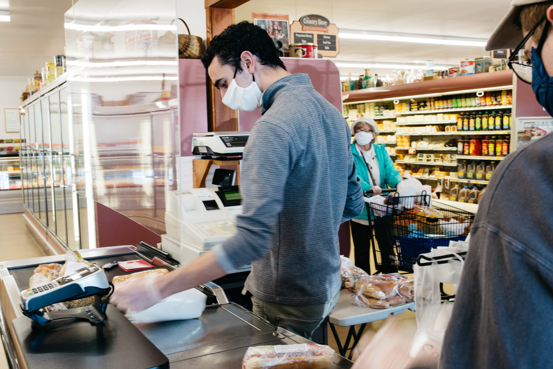 A cashier wears gloves and a face mask while assisting a customer at The Country Store on May 9, 2020, in Mount Joy, Pa.