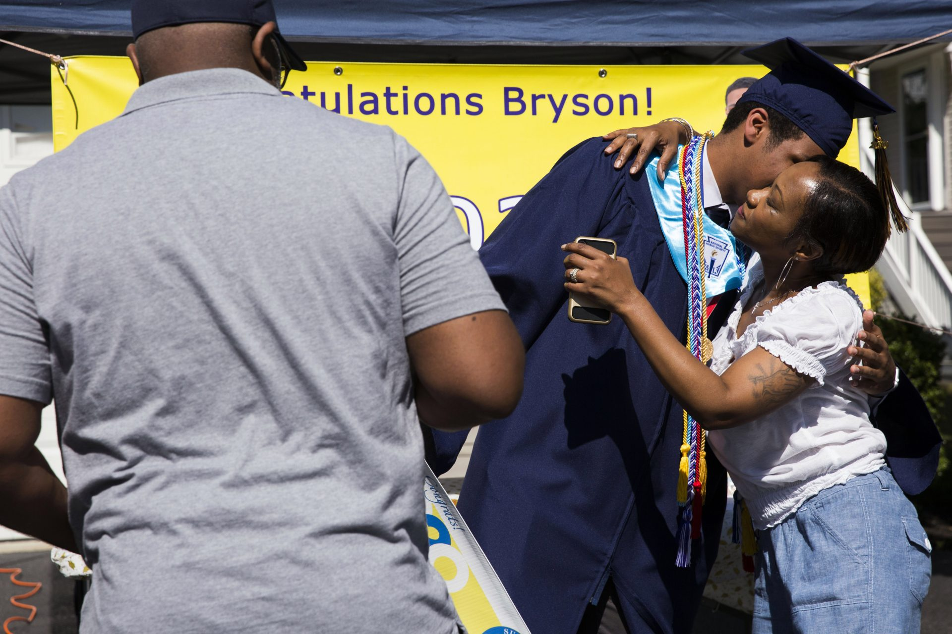 Bryson Eldridge (center) receives congratulations from his parents, Elaina and Greg, after receiving his high school diploma via a modified graduation ceremony on June 9, 2020.