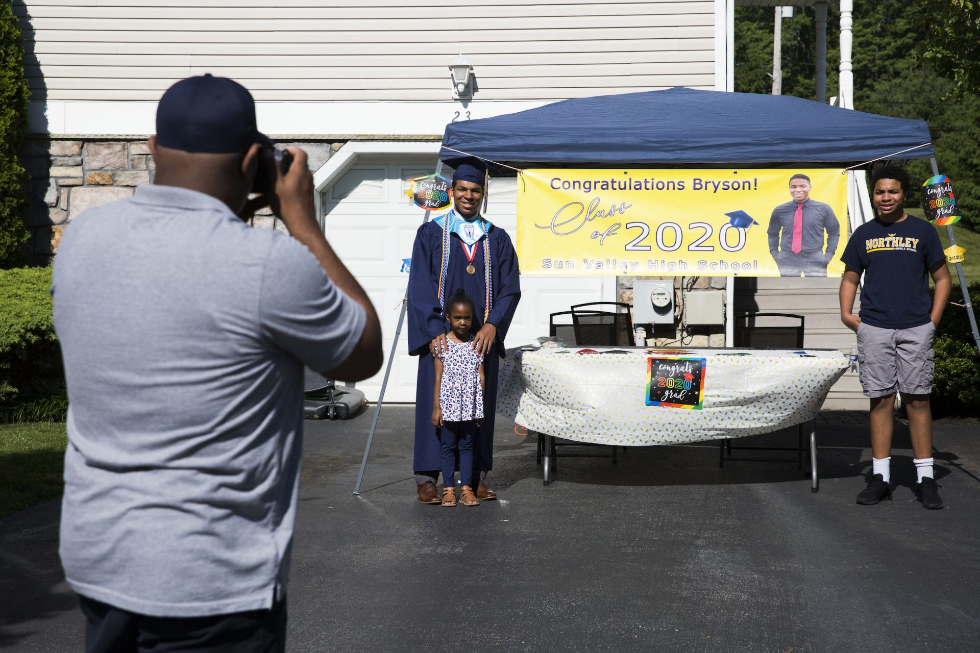 Greg Eldridge (left) takes a photo of his kids (from left) Bryson, Kennedy, and Blaise in the driveway of their home on June 9, 2020. Bryson Eldridge is graduating from Sun Valley High School this year and will be attending the University of Scranton in the fall. (Rachel Wisniewski for WHYY)