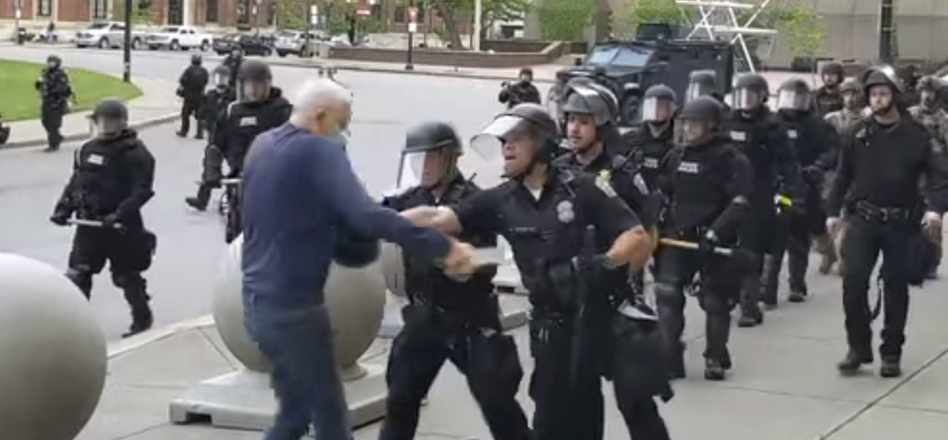 """In this image from video provided by WBFO, a Buffalo police officer appears to shove a man who walked up to police Thursday, June 4, 2020, in Buffalo, N.Y. Video from WBFO shows the man appearing to hit his head on the pavement, with blood leaking out as officers walk past to clear Niagara Square. Buffalo police initially said in a statement that a person """"was injured when he tripped & fell,"""" WIVB-TV reported, but Capt. Jeff Rinaldo later told the TV station that an internal affairs investigation was opened."""