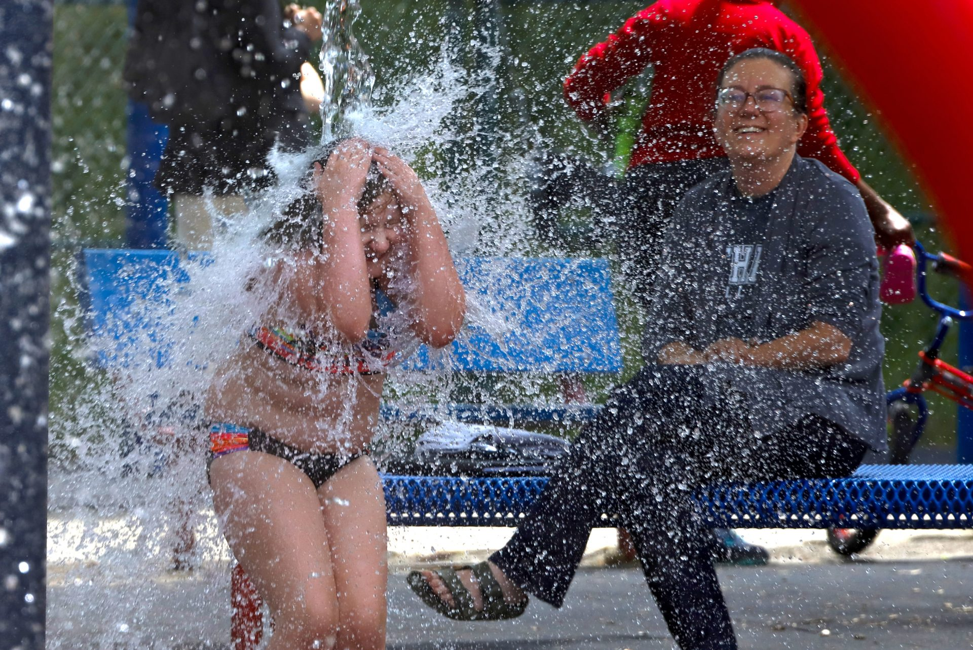 Katie Pawlowski, 8, left, plays in the spray park in the Squirrel Hill neighborhood of Pittsburgh with her mother Stephanie looking on, Monday, June 15, 2020. It was the first day that the City of Pittsburgh spray parks were reopened with Allegheny County now having been in the 'green' phase for two weeks.
