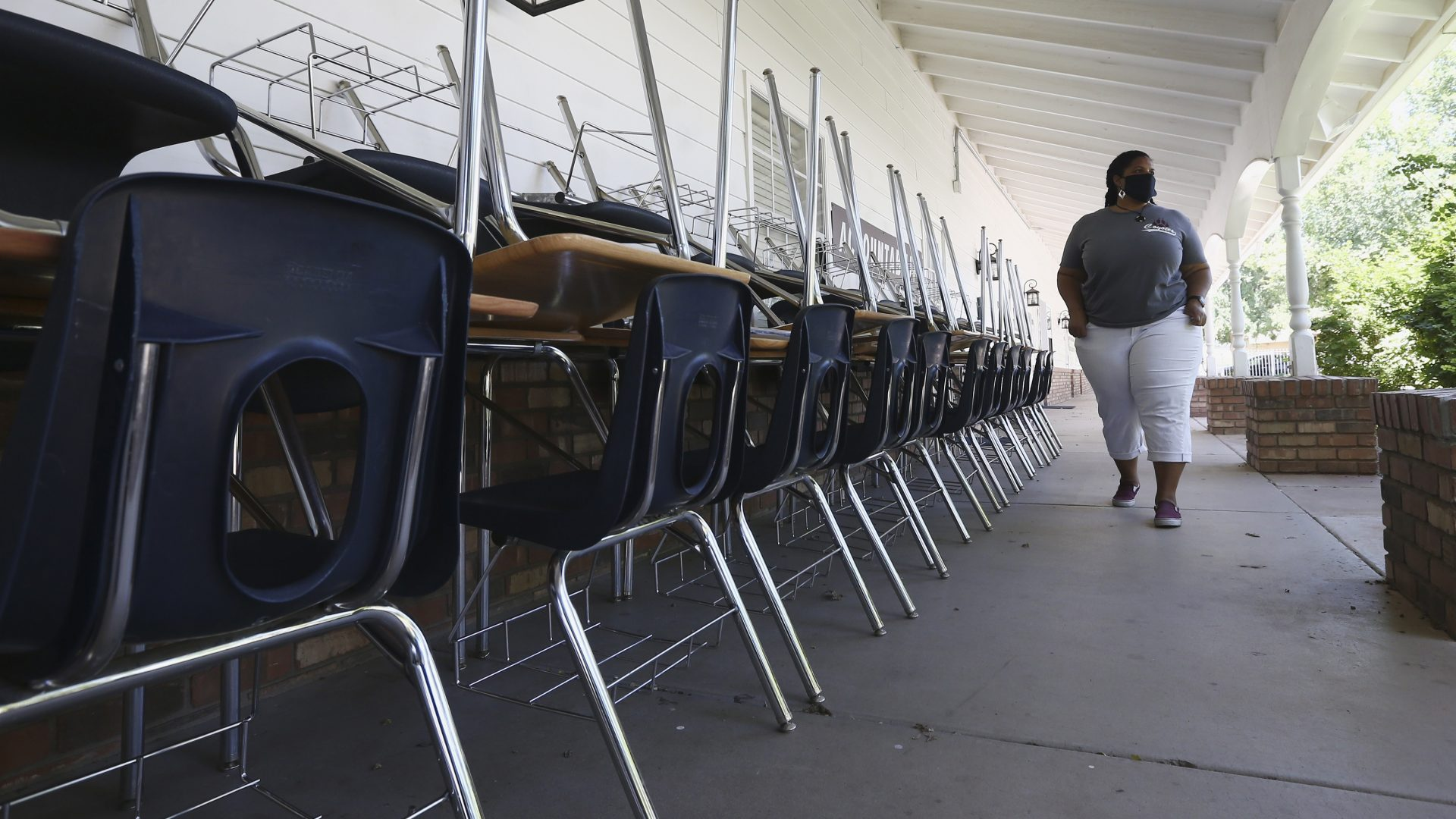 Kristina Washington, special education staff member at Desert Heights Preparatory Academy, walks past desks and chairs at the closed Glendale, Ariz., school in early June.