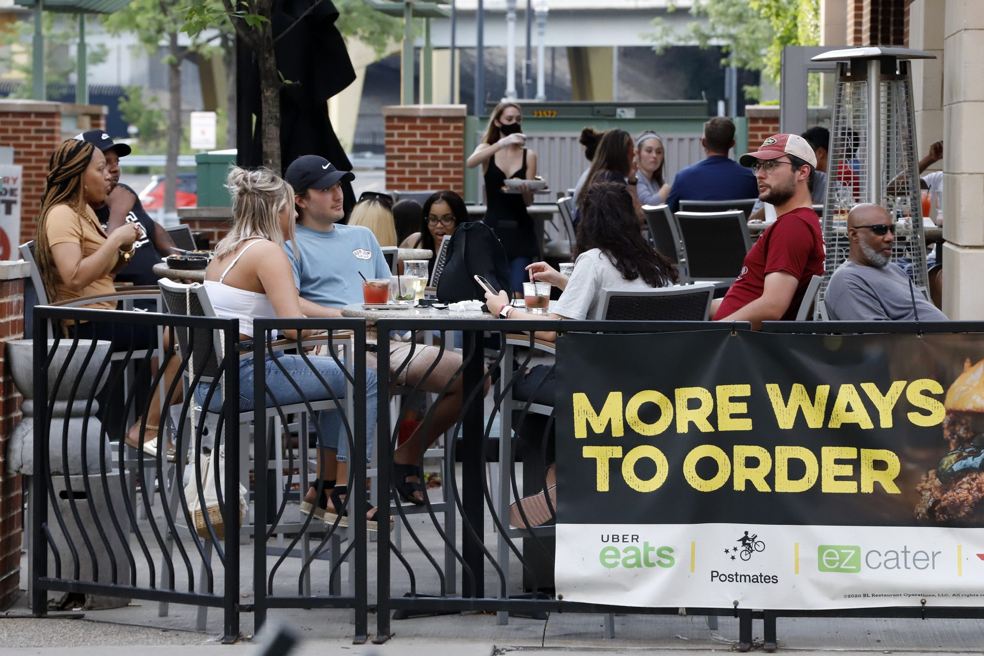 People gather at tables outside Bar Louie on the Northside of Pittsburgh Sunday, June 28, 2020. In response to the recent spike in COVID-19 cases in Allegheny County, health officials are ordering all bars and restaurants in the county to stop the sale of alcohol for on-site consumption beginning on June 30.