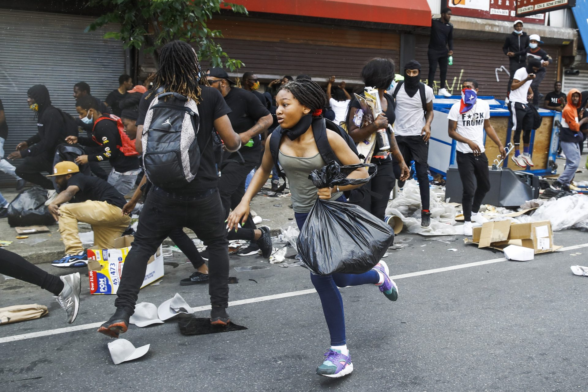 People run from the area as police officers approach stores that were broken into as protests continue on Sunday, May 31, 2020, in Philadelphia. Protests were held throughout the country over the death of Floyd, a black man who died after being restrained by Minneapolis police officers on May 25.