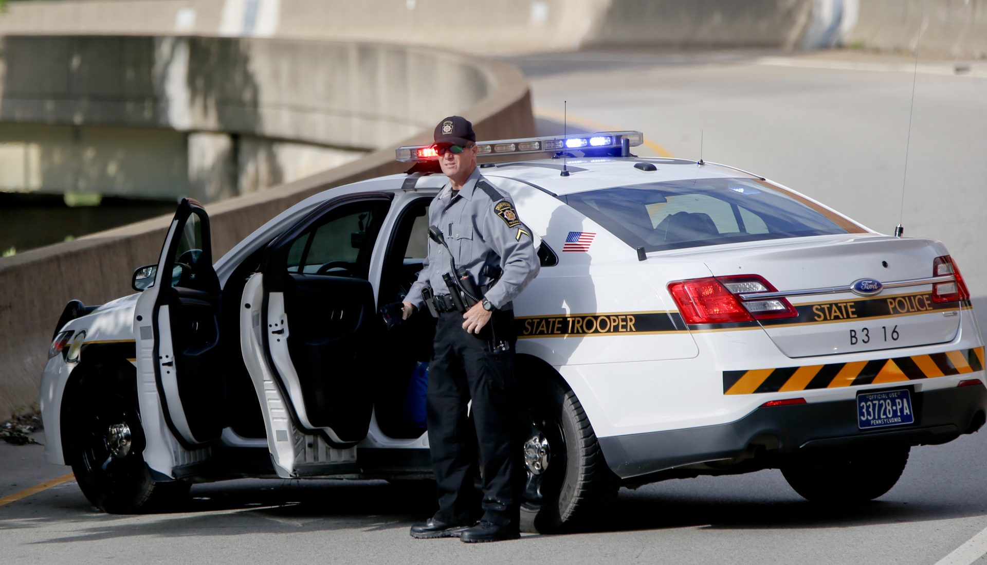 A Pennsylvania State Trooper stands beside his vehicle parked on the entrance ramp to Interstate 376 out of Pittsburgh as protesters block an intersection in downtown Pittsburgh, on Tuesday, June 26, 2018.