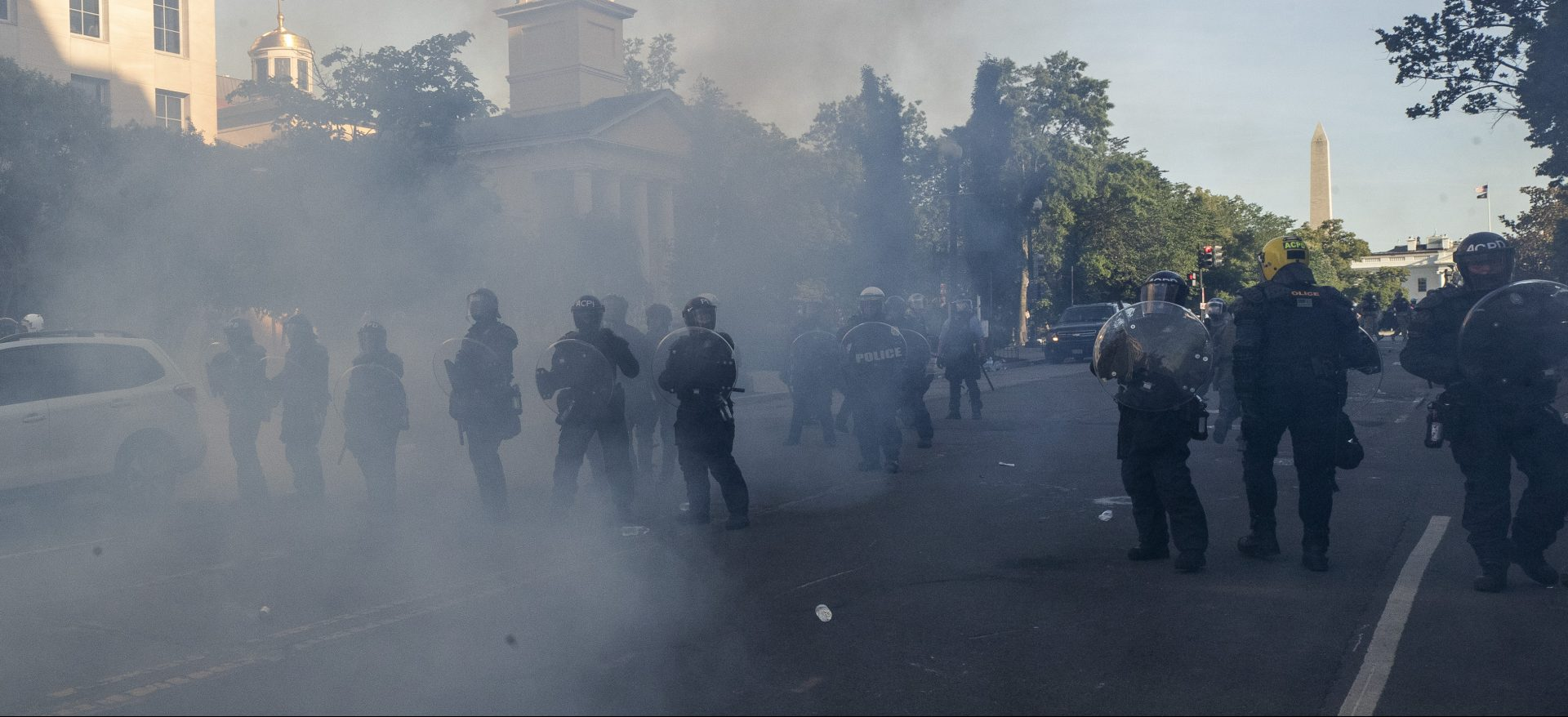 Tear gas floats in the air as a line of police move demonstrators away from St. John's Church across Lafayette Park from the White House, as they gather to protest the death of George Floyd, Monday, June 1, 2020, in Washington. Floyd died after being restrained by Minneapolis police officers.