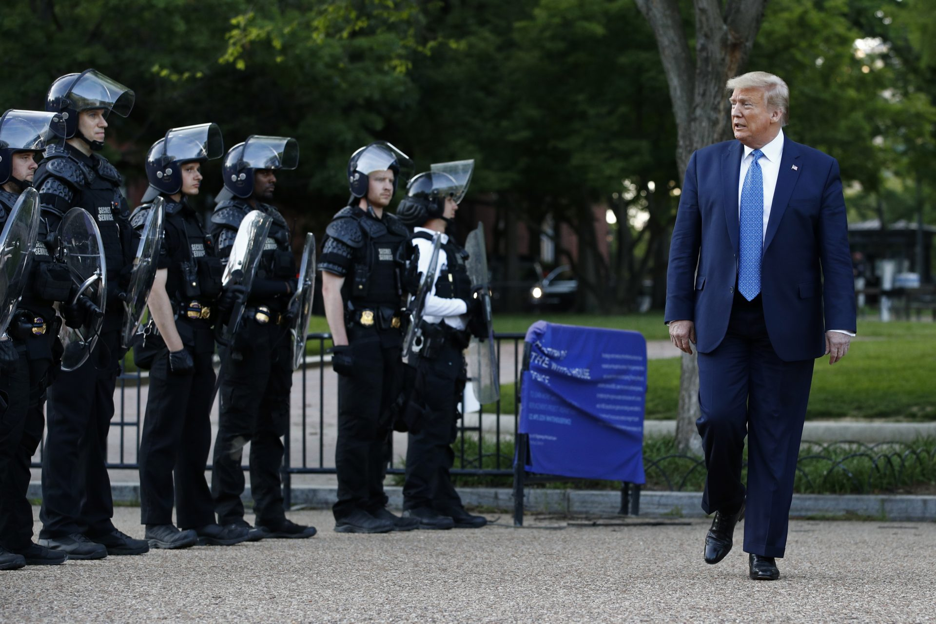 President Donald Trump walks past police in Lafayette Park after visiting outside St. John's Church across from the White House Monday, June 1, 2020, in Washington. Part of the church was set on fire during protests on Sunday night.