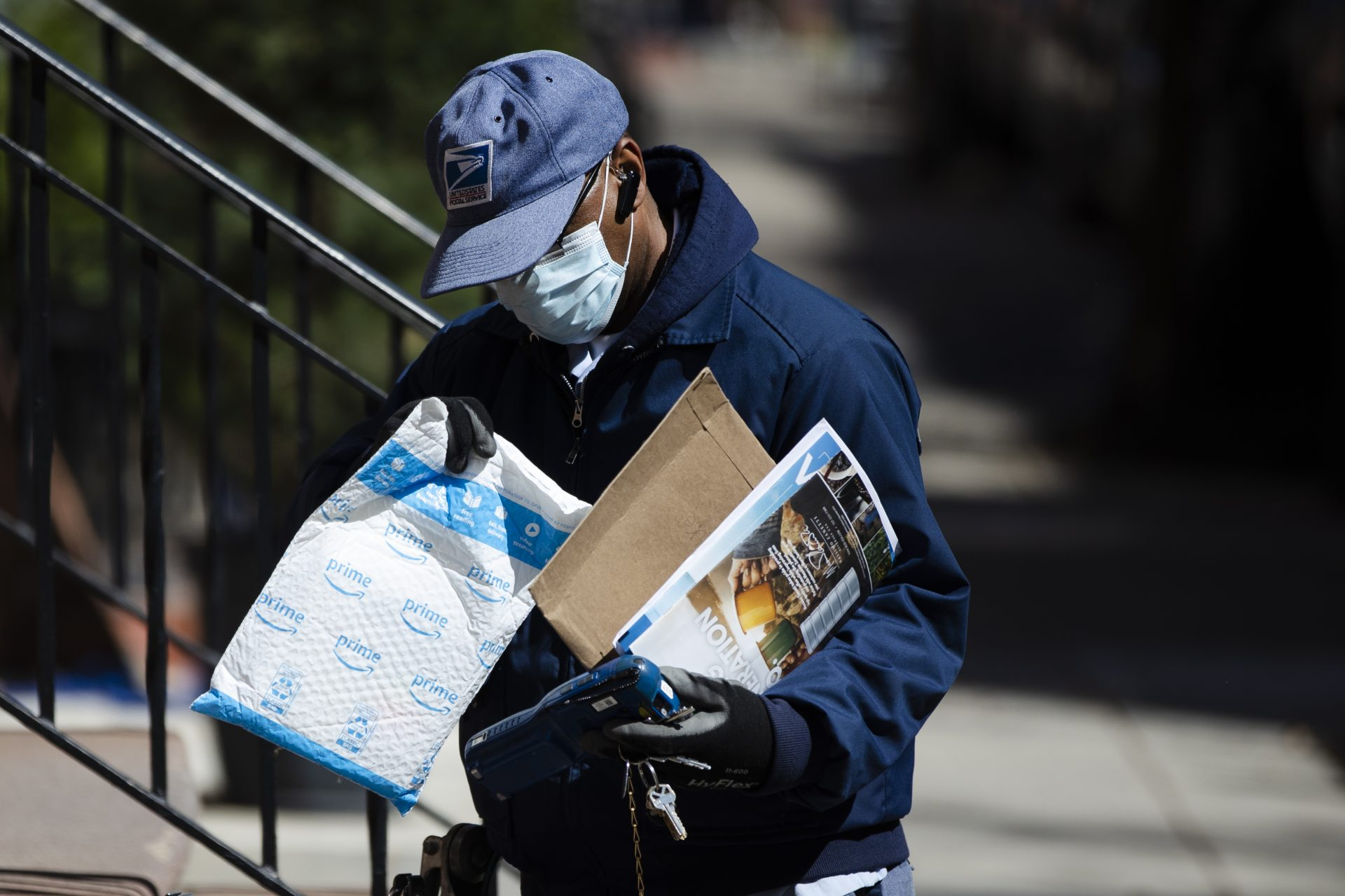 A United States Postal worker makes a delivery with gloves and a mask in Philadelphia, Thursday, April 2, 2020.