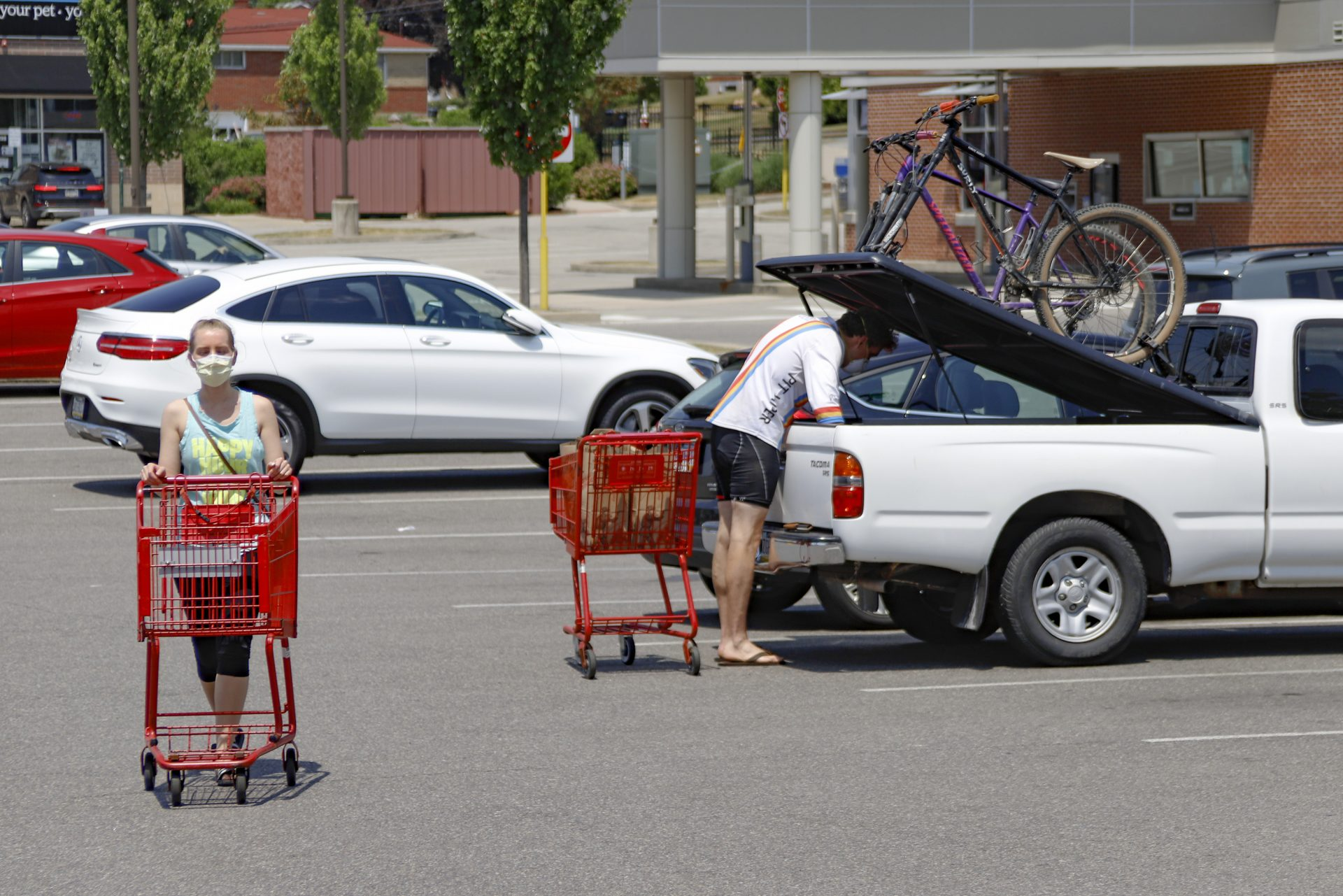 A woman and man wear COVID-19 protective masks as she pushes her shopping cart and a man loads his truck in a parking lot, Friday, July 3, 2020, in McCandless, Pa. Gov. Tom Wolf's more expansive mask order issued this week as the coronavirus shows new signs of life in Pennsylvania and the July Fourth holiday starts has been met with hostility from Republicans objecting to the Democrat's use of power or even to wearing a mask itself.