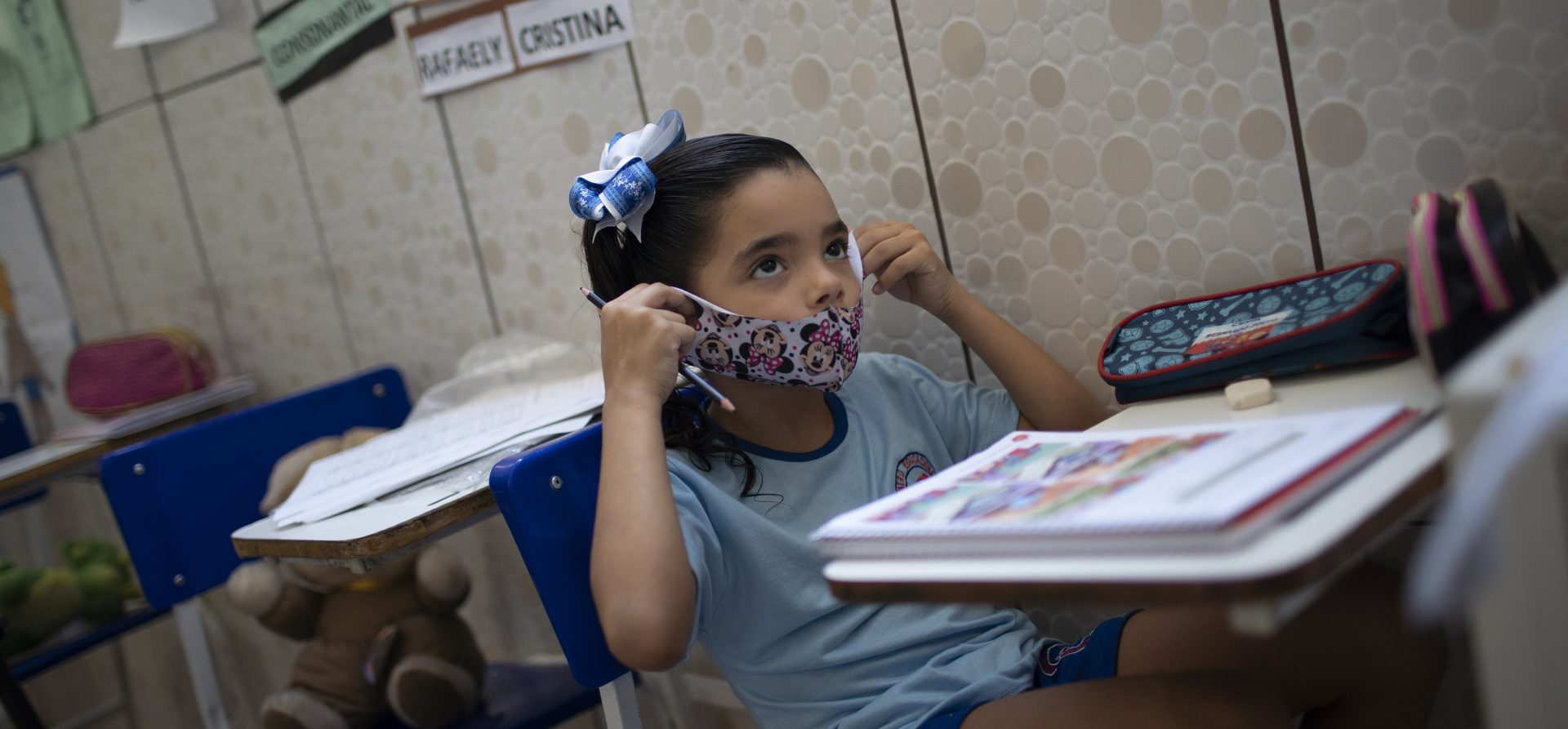 Rafaely de Melo puts on her protective mask during a class at the Pereira Agustinho daycare, nursery school and pre-school, after it reopened amid the new coronavirus pandemic in Duque de Caxias, Monday, July 6, 2020. The city of Manaus in the Amazon rainforest and Duque de Caxias in Rio de Janeiro's metropolitan region, became on Monday the first Brazilian cities to resume in-person classes at private schools since the onset of the COVID-19 pandemic, according to the nation's private school federation.