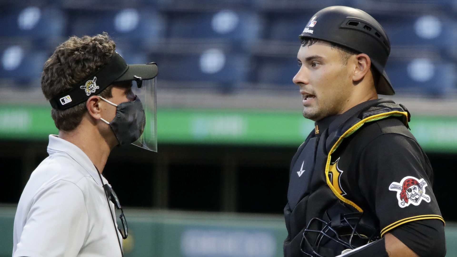 Pittsburgh Pirates catcher Luke Maile, right, talks with a trainer during an intrasquad game during the team's baseball practice at PNC Park in Pittsburgh, Wednesday, July 15, 2020.