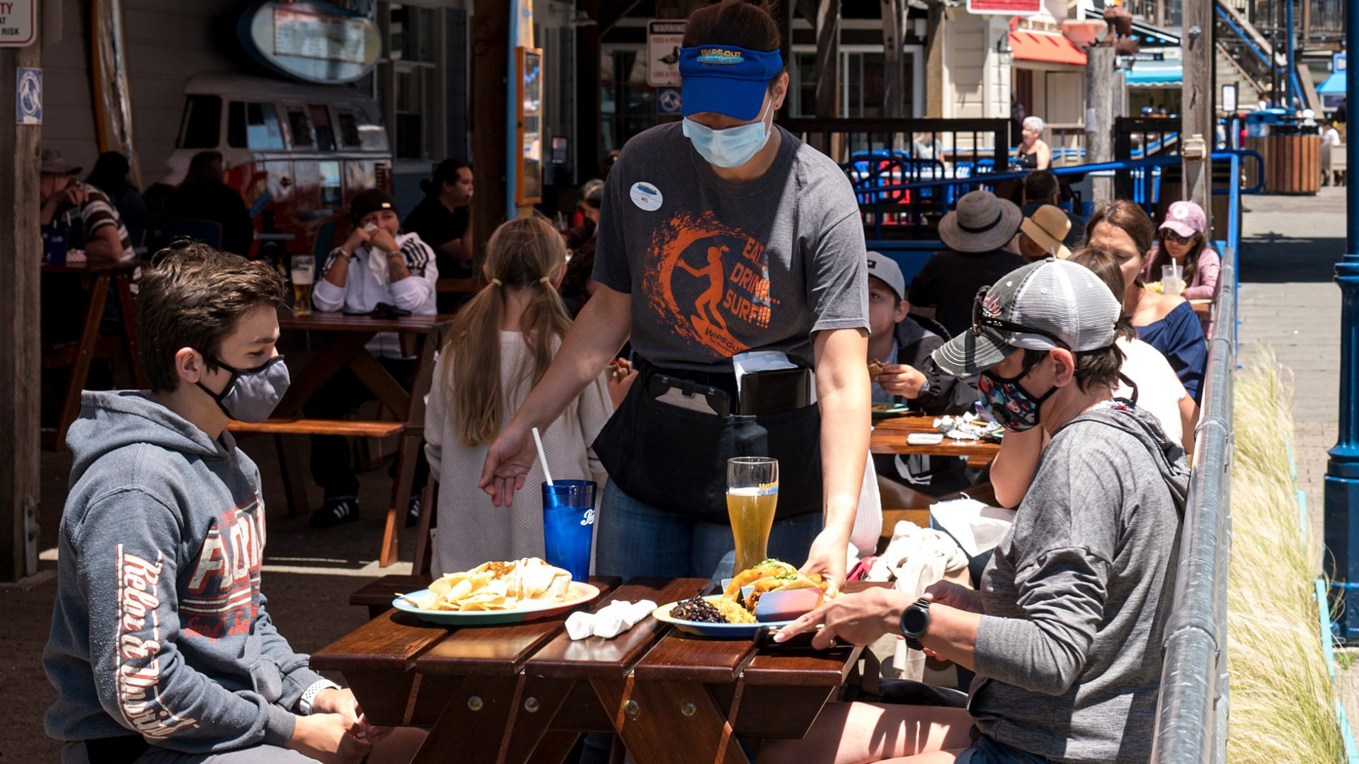 More than 20 U.S. states now require face masks, as officials hope to curb a sharp rise in new coronavirus cases. Here, patrons wear masks as they sit in the outdoor patio of a restaurant on Pier 39 at Fisherman's Wharf in San Francisco.