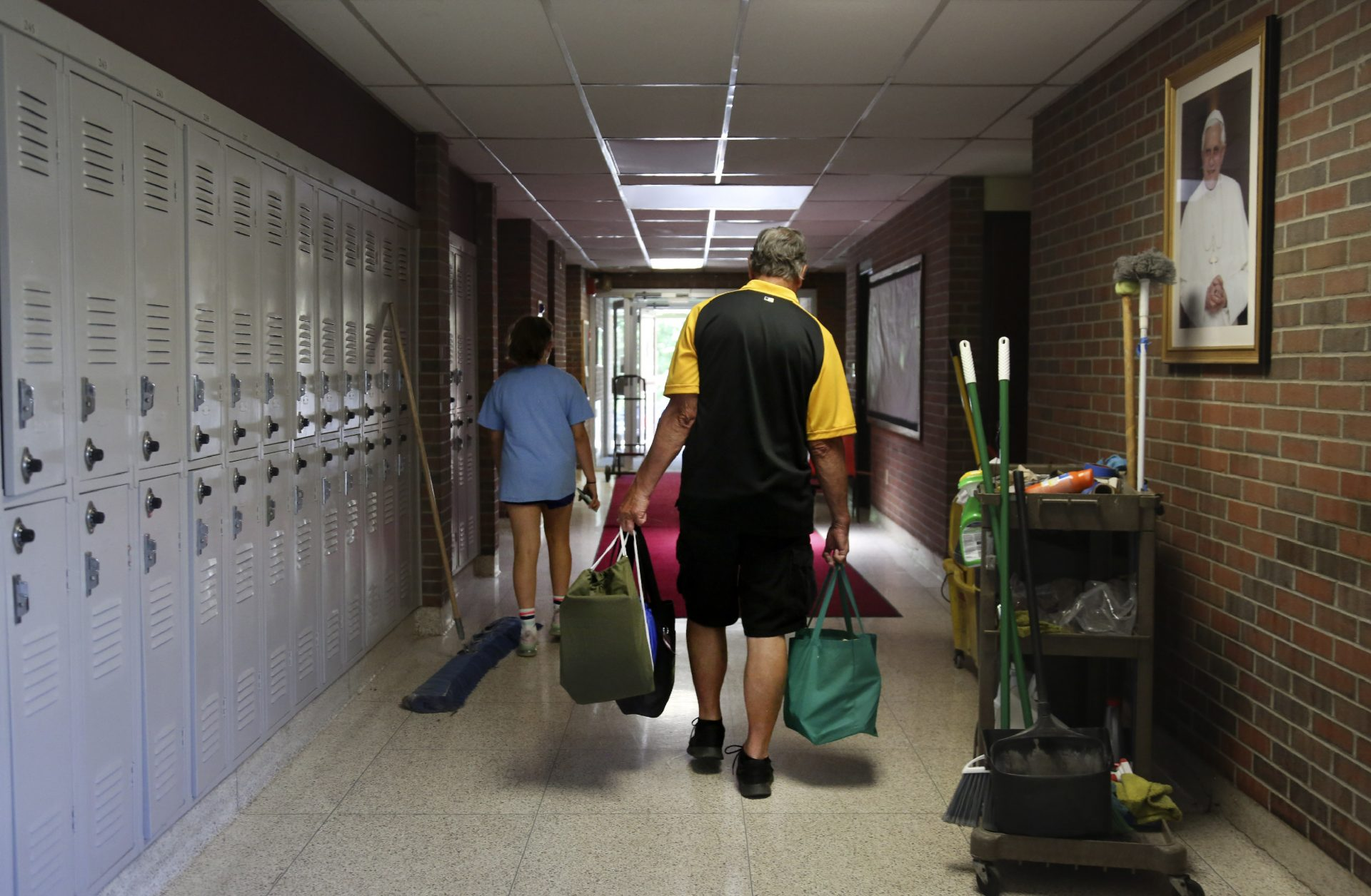 Cesa Pusateri, 12, and her grandfather, Timothy Waxenfelter, principal of Quigley Catholic High School, leave with his collection of speech and debate books after the recent closure of the school in Baden, Pa., Monday, June 8, 2020.