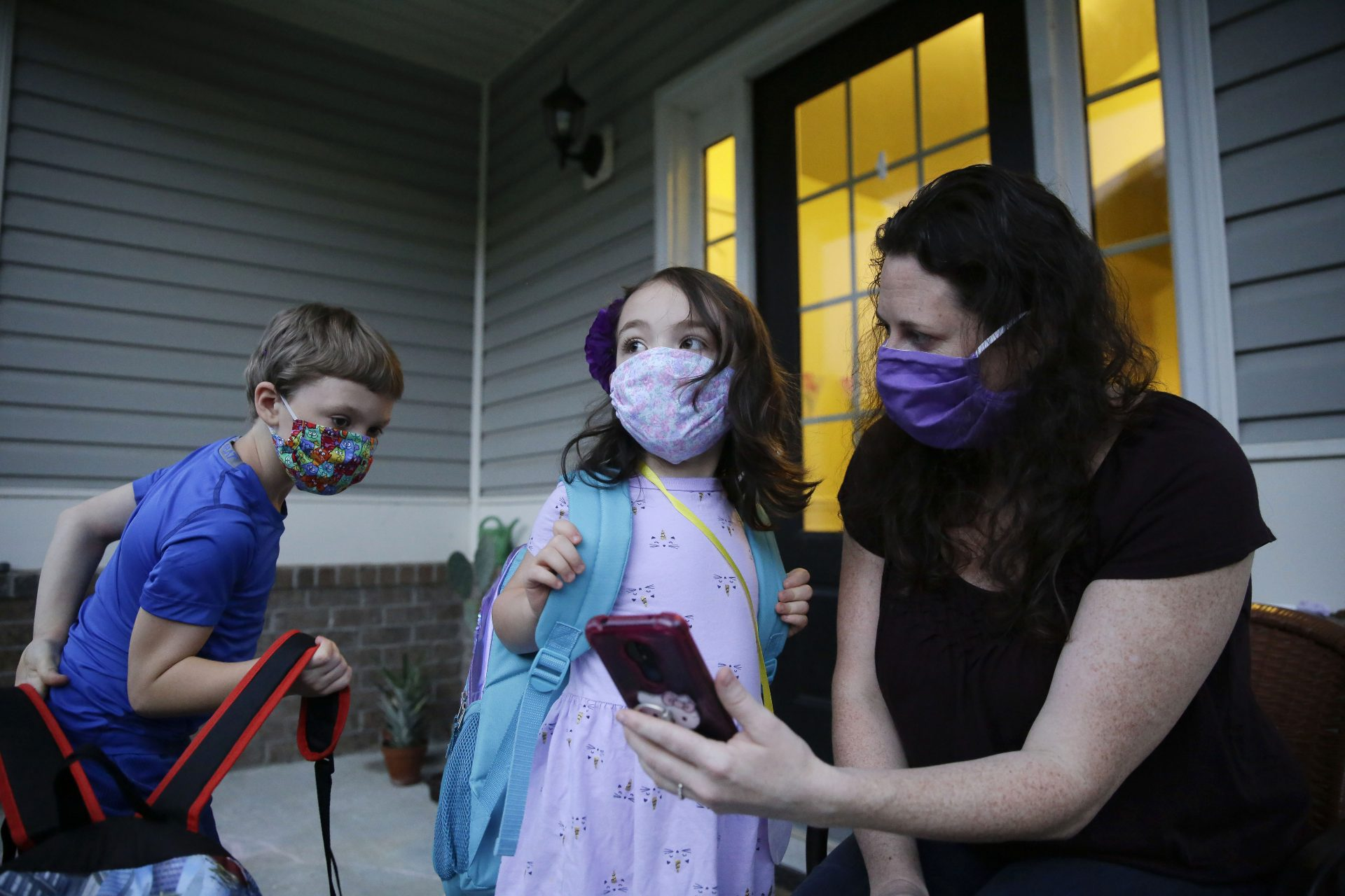 Rachel Adamus, right, shows her children, Paul, left, and Neva, 5, center, an app on her phone showing when the school bus will arrive near their home, on Monday, Aug. 3, 2020, in Dallas, Ga. The Adamus children are among tens of thousands of students in Georgia and across the nation who were set to resume in-person school Monday for the first time since March.
