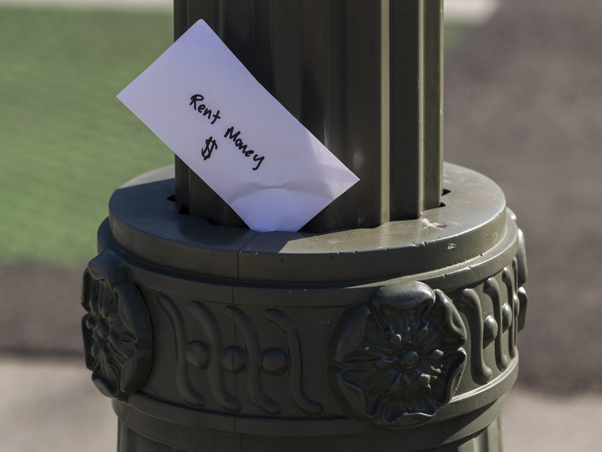"An envelope labeled ""Rent Money"" is left tucked in a lighting pole in Los Angeles on April 1. President Trump's new executive order to prevent evictions isn't enough and Congress needs to act, housing activists say."