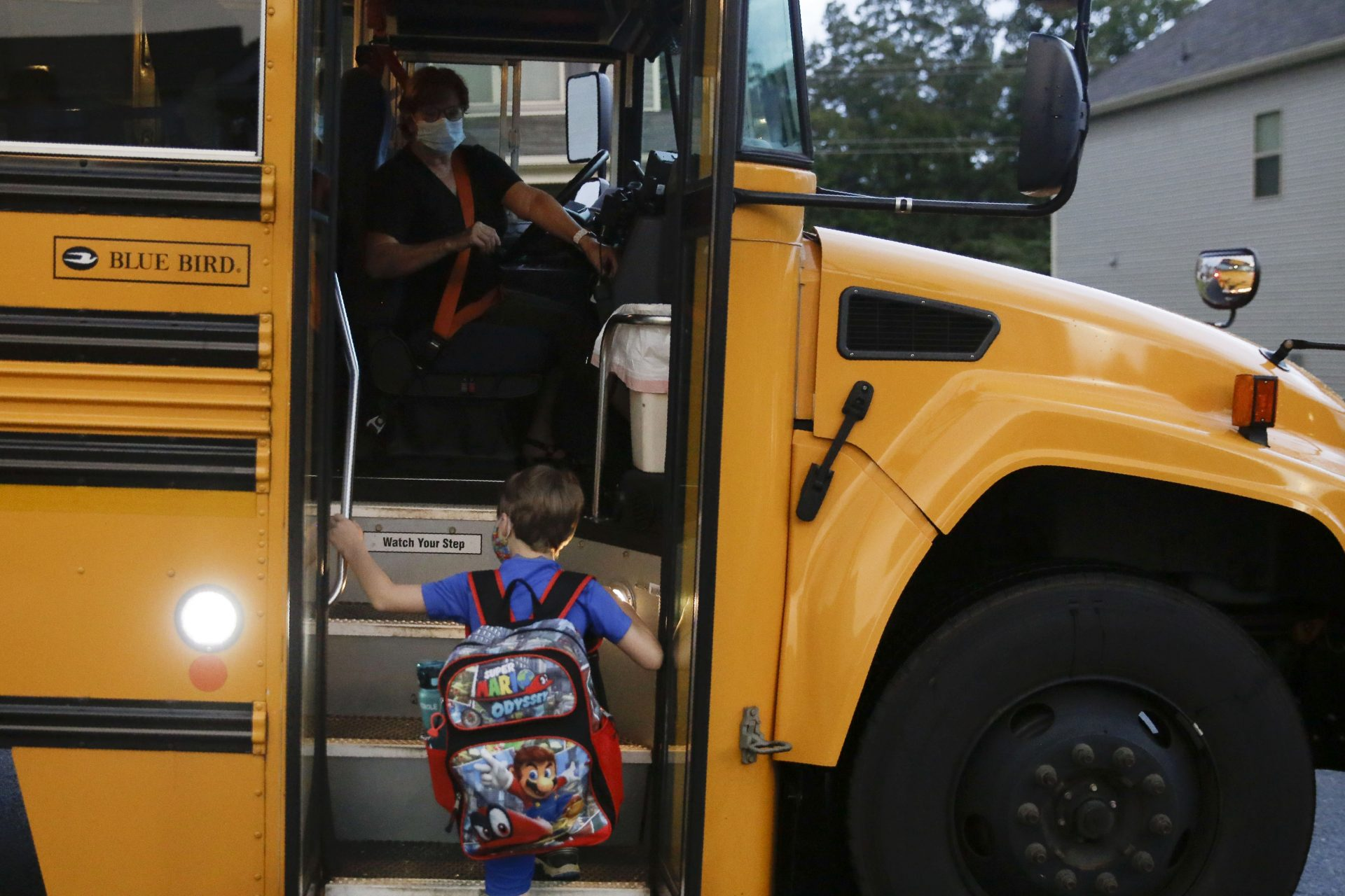 Paul Adamus, 7, climbs the stairs of a bus before the fist day of school on Monday, Aug. 3, 2020, in Dallas, Ga. Adamus is among tens of thousands of students in Georgia and across the nation who were set to resume in-person school Monday for the first time since March.