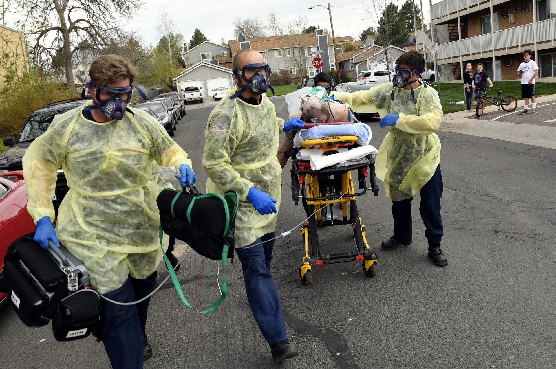 Firefighters in Littleton, Colo., move a patient on a gurney to an ambulance to take him to the hospital in May.