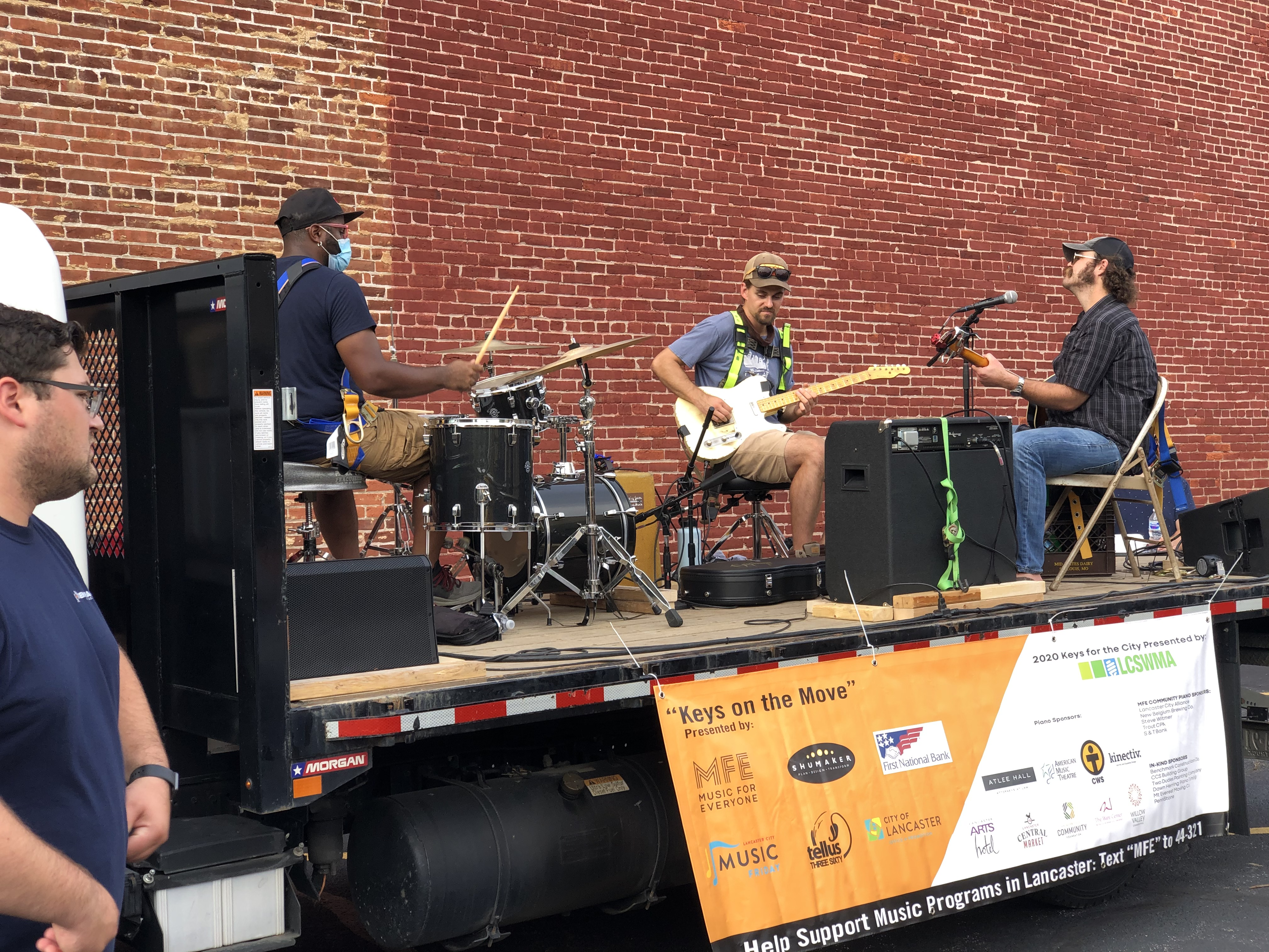 Andy Mowatt and his band performing on a flatbed truck.