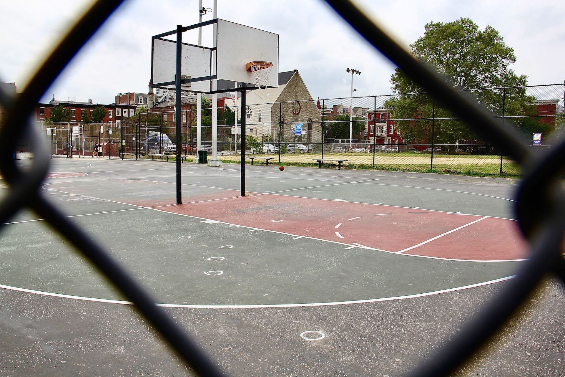 The basketball court at Roberto Clemente Playground is padlocked after five people were shot, two fatally. Chalk circles mark where bullet casings fell.