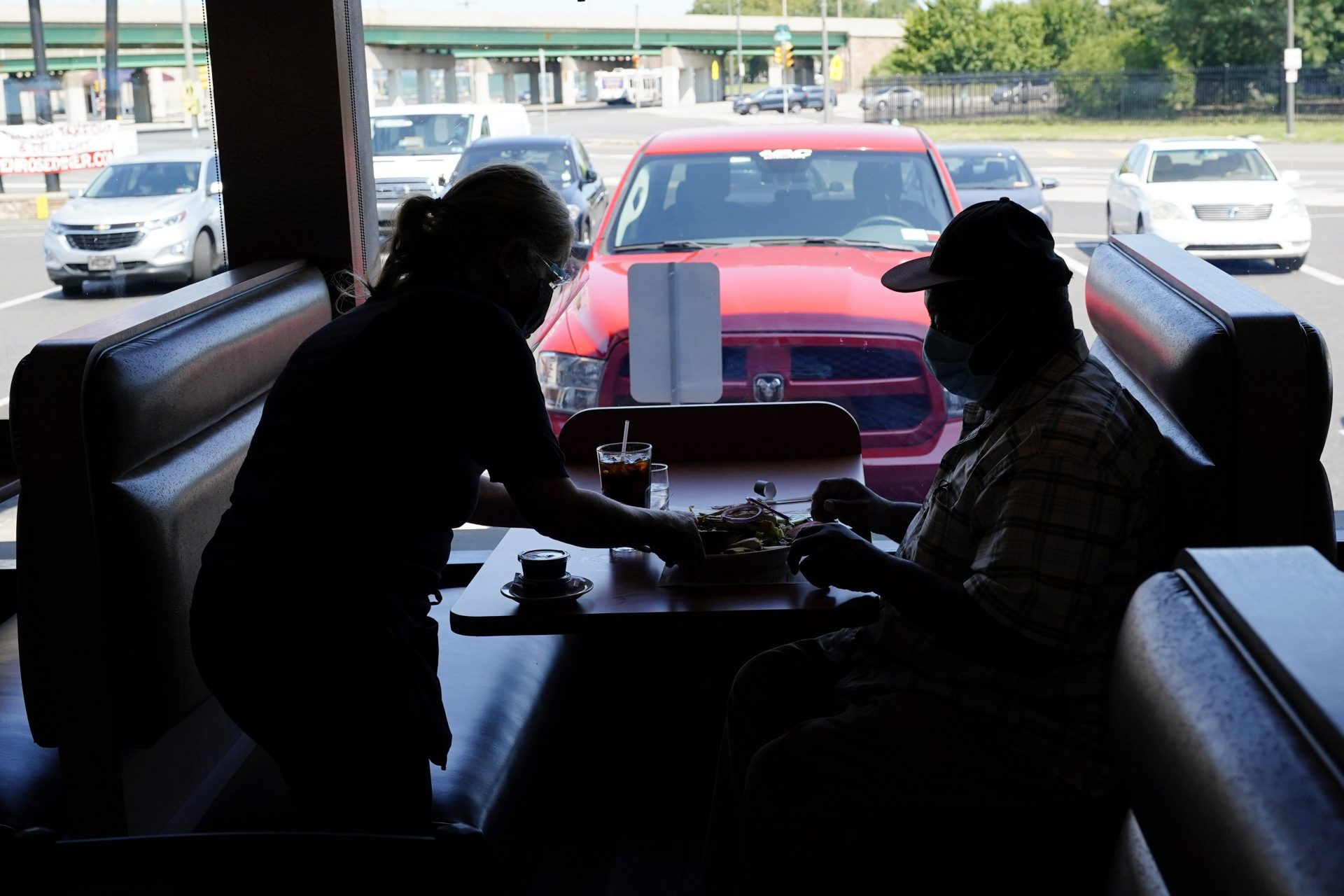 A waitress serves lunch to a customer at the Penrose Diner during the coronavirus pandemic, Tuesday, Sept. 8, 2020, in Philadelphia.