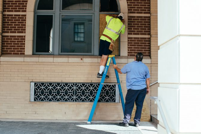 Construction workers repair broken windows at the Lancaster City Police Bureau building following a night of protests on September 14, 2020.