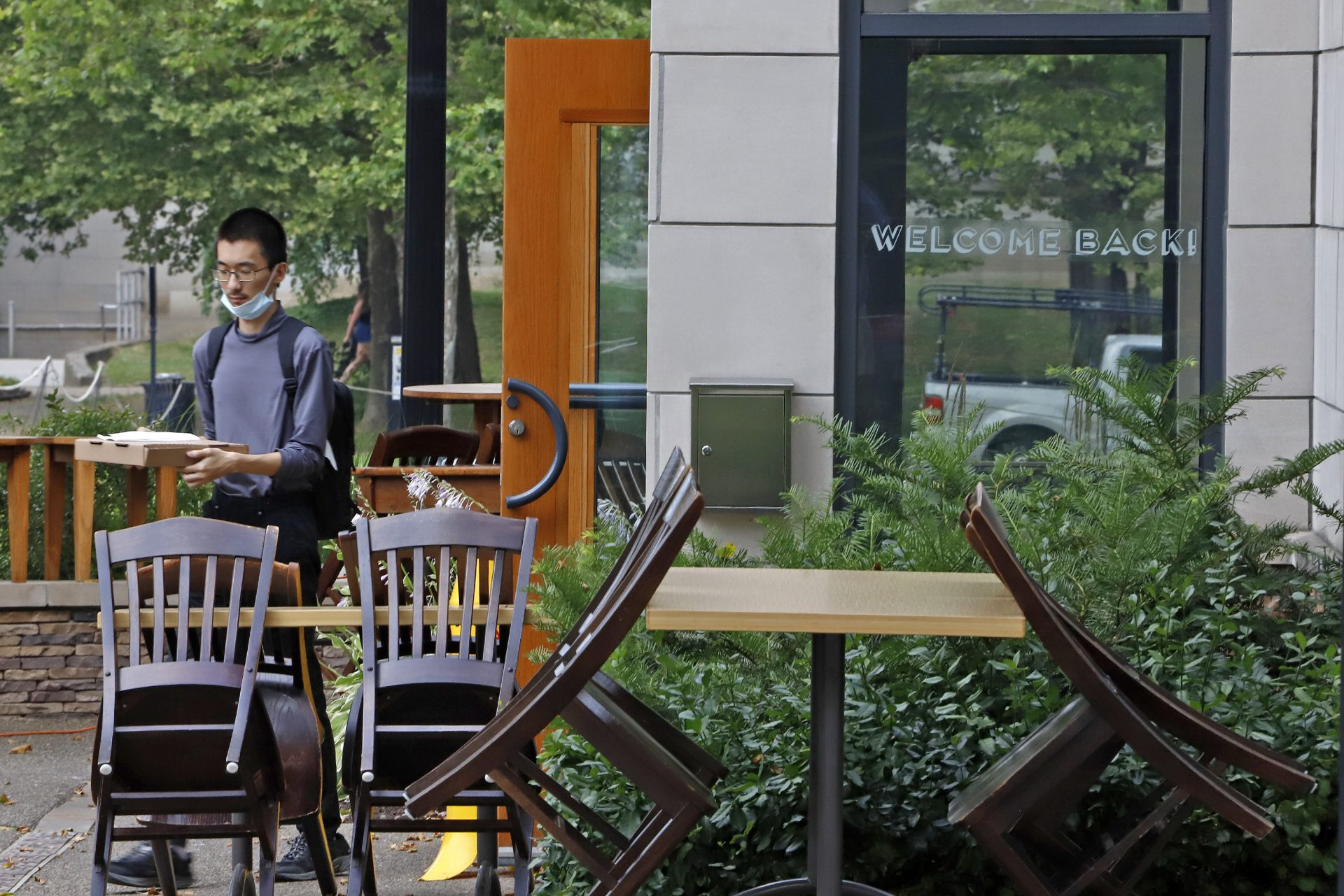 A man walks out of the Porch restaurant with his takeout order on Thursday, July 9, 2020 in the Oakland neighborhood of Pittsburgh. Due to a spike in COVID-19 infections, service at restaurants has been limited to takeout for the past week. Beginning Friday, restaurants will re-open for outside dining only.
