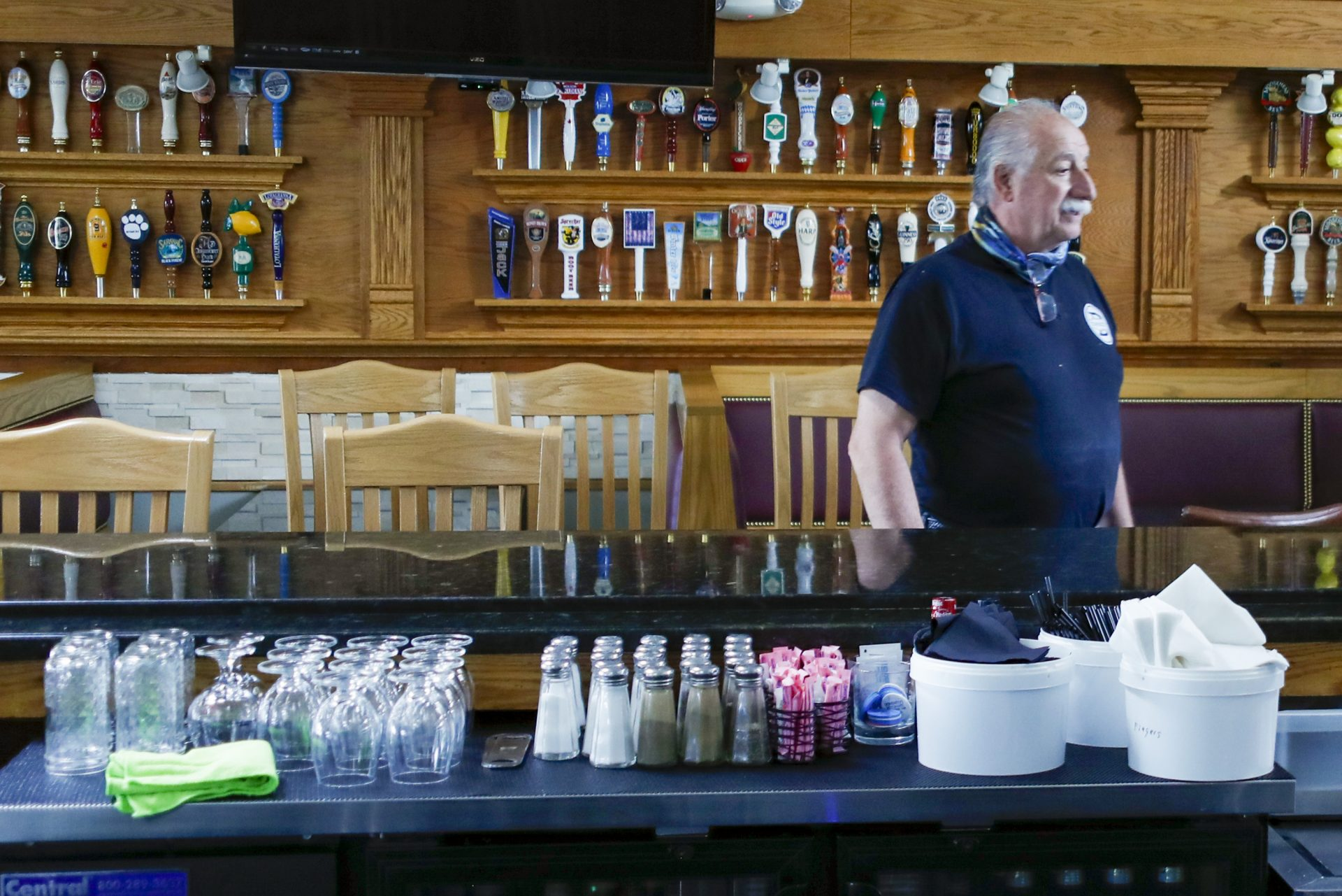 FILE PHOTO: Dominic Lombardo, owner of Domenicos restaurant, looks over the bar area, with the barstools separated, Thursday, June 4, 2020, in Cranberry Township, Pa., the day before patrons were again permitted to dine inside as COVID-19 restrictions loosened in the region.